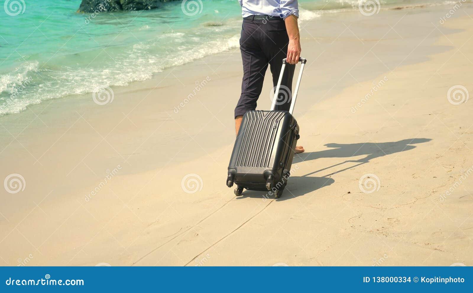 O homem de negócios com uma mala de viagem vai em um Sandy Beach branco conceito de freelancing, férias