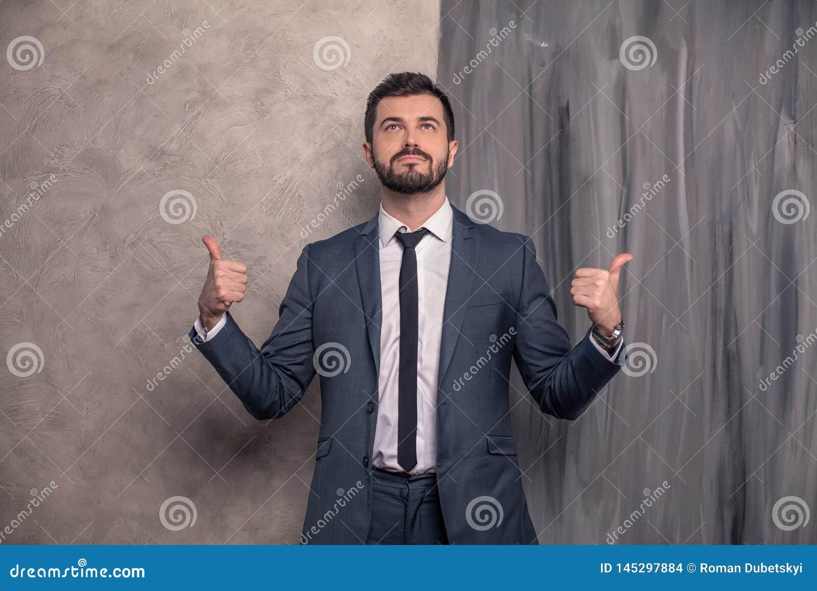 O homem de negócios considerável bonito está estando em seu escritório que aponta os dedos aos lados e que olha acima terno v