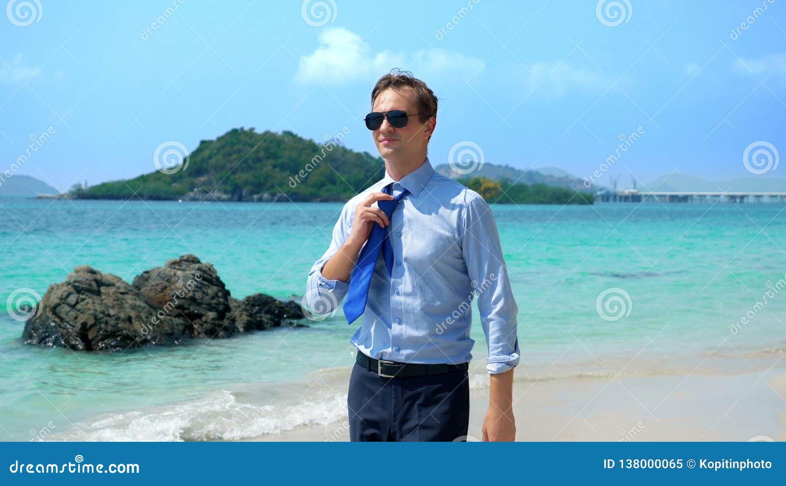 O homem de negócios considerável nos óculos de sol andou ao longo de uma praia tropical, decolando seu laço