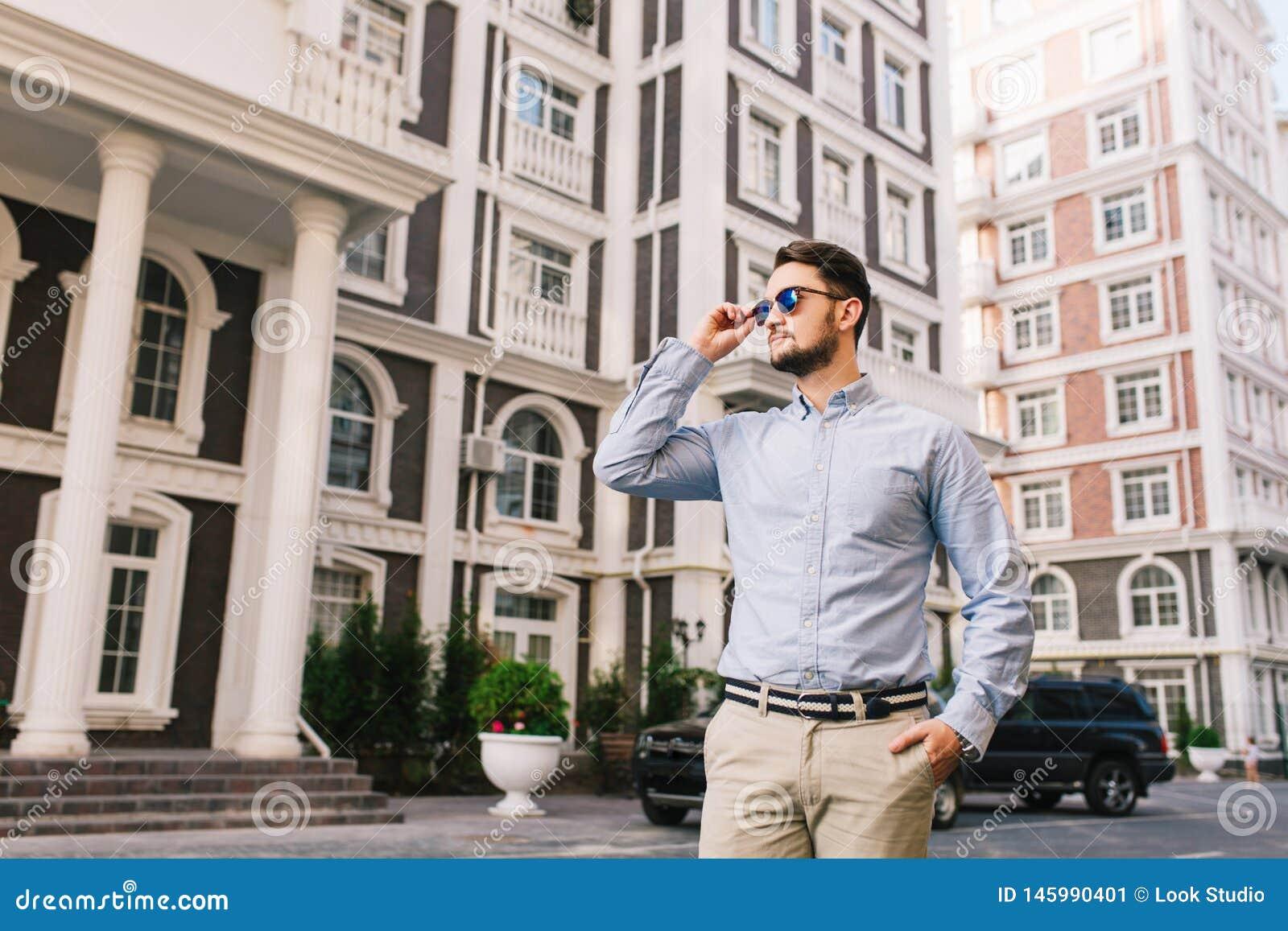 O homem de negócios considerável nos óculos de sol está andando em torno do quarto britânico Guarda a mão no bolso, olhando seria