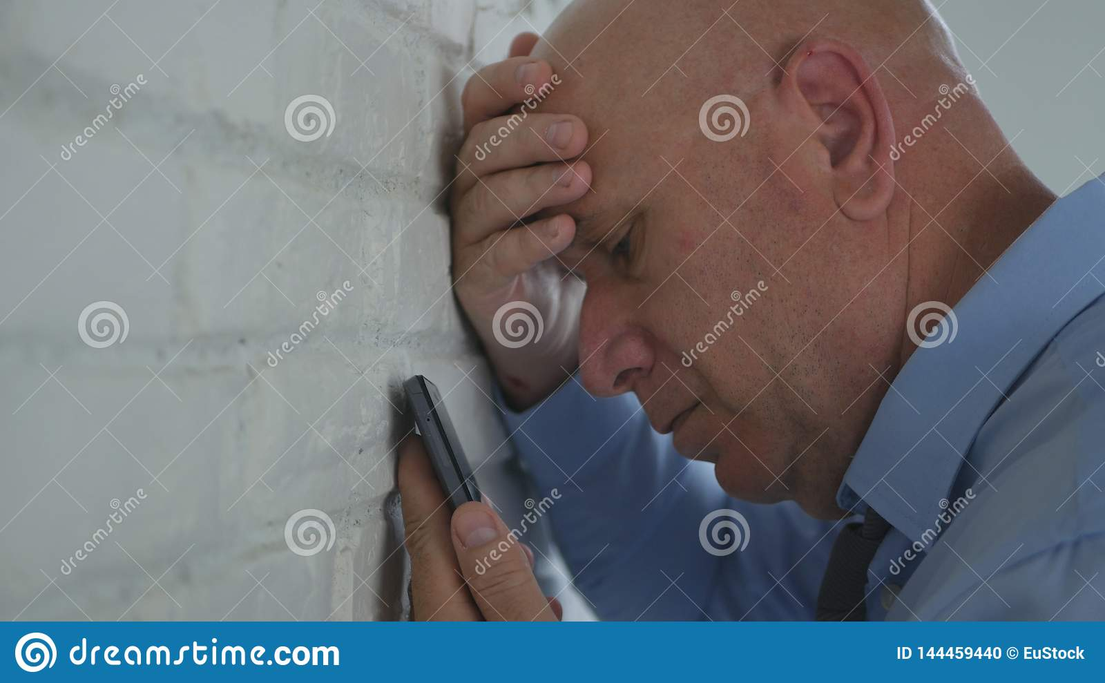 O homem de negócios decepcionado no escritório leu notícias financeiras más no telefone celular