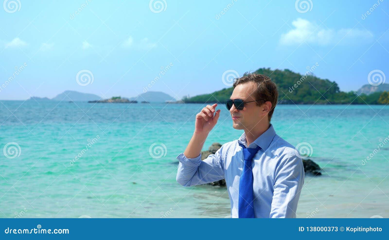 O homem de negócios em uma camisa e em um laço, nos óculos de sol vai em um Sandy Beach branco conceito freelancing, férias