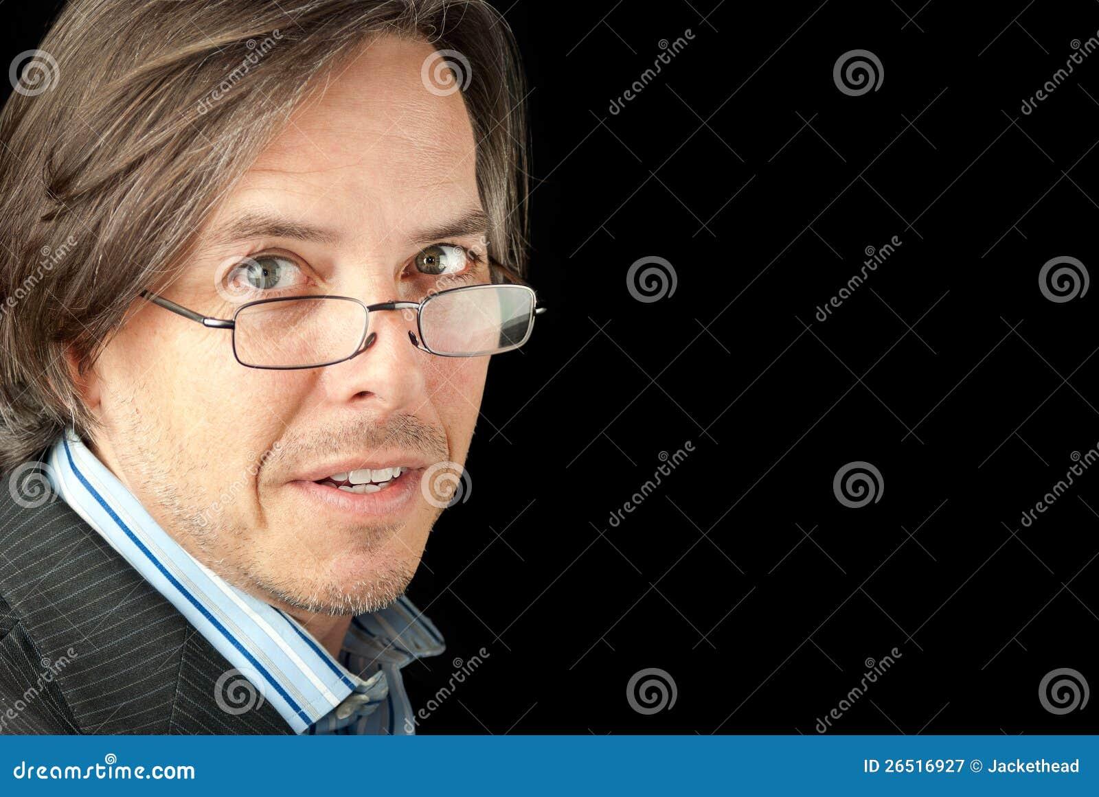 O homem de negócios em vidros de leitura olha à câmera