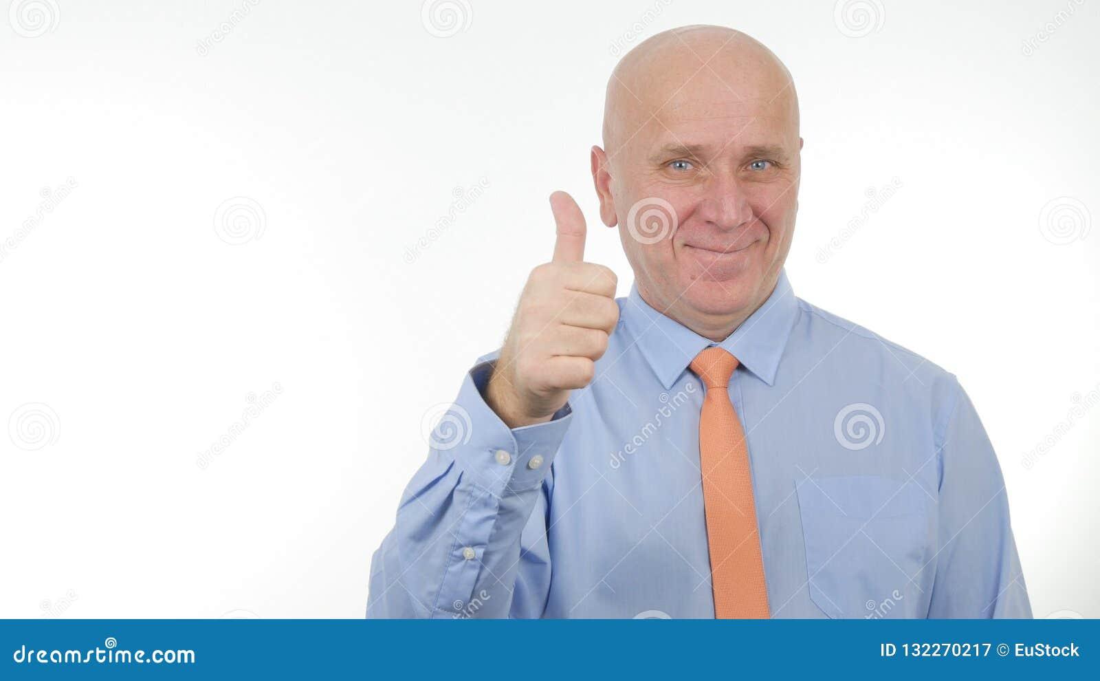 O homem de negócios entusiástico Smile e para fazer os polegares acima de um bom trabalho gesticula