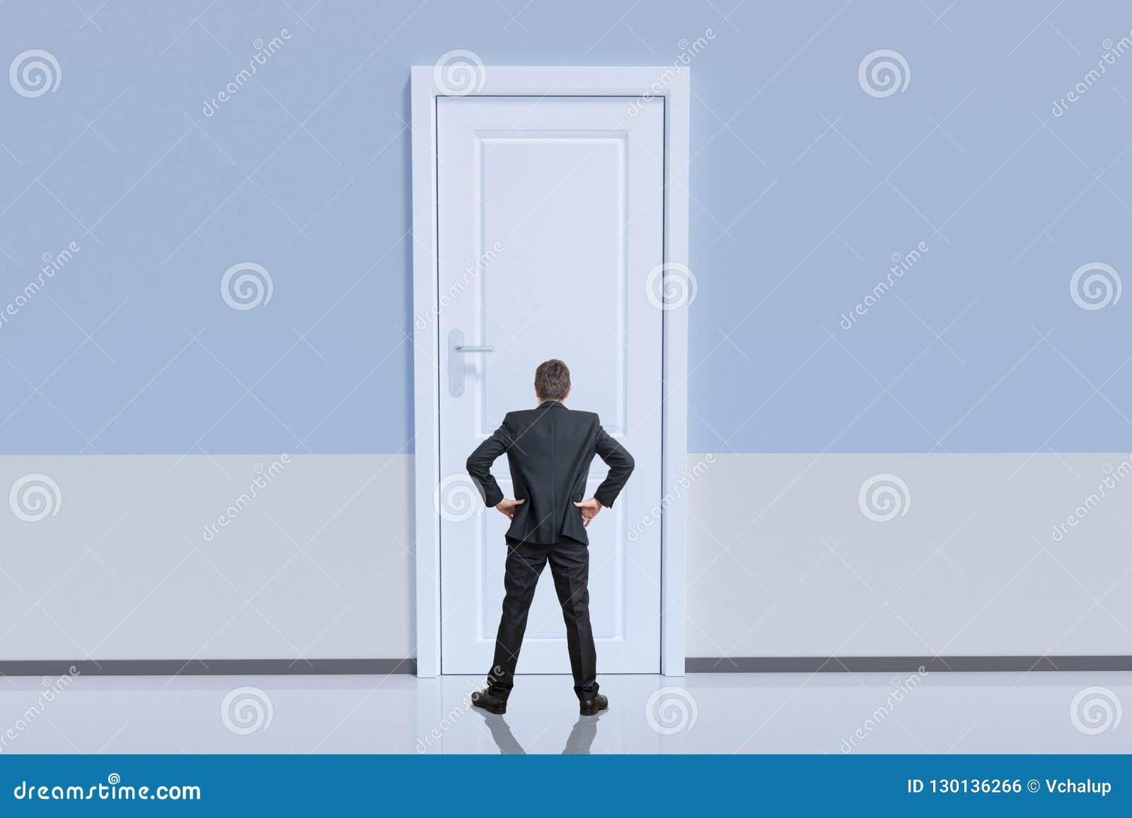 O homem de negócios está estando atrás da porta grande Conceito da oportunidade e do desafio