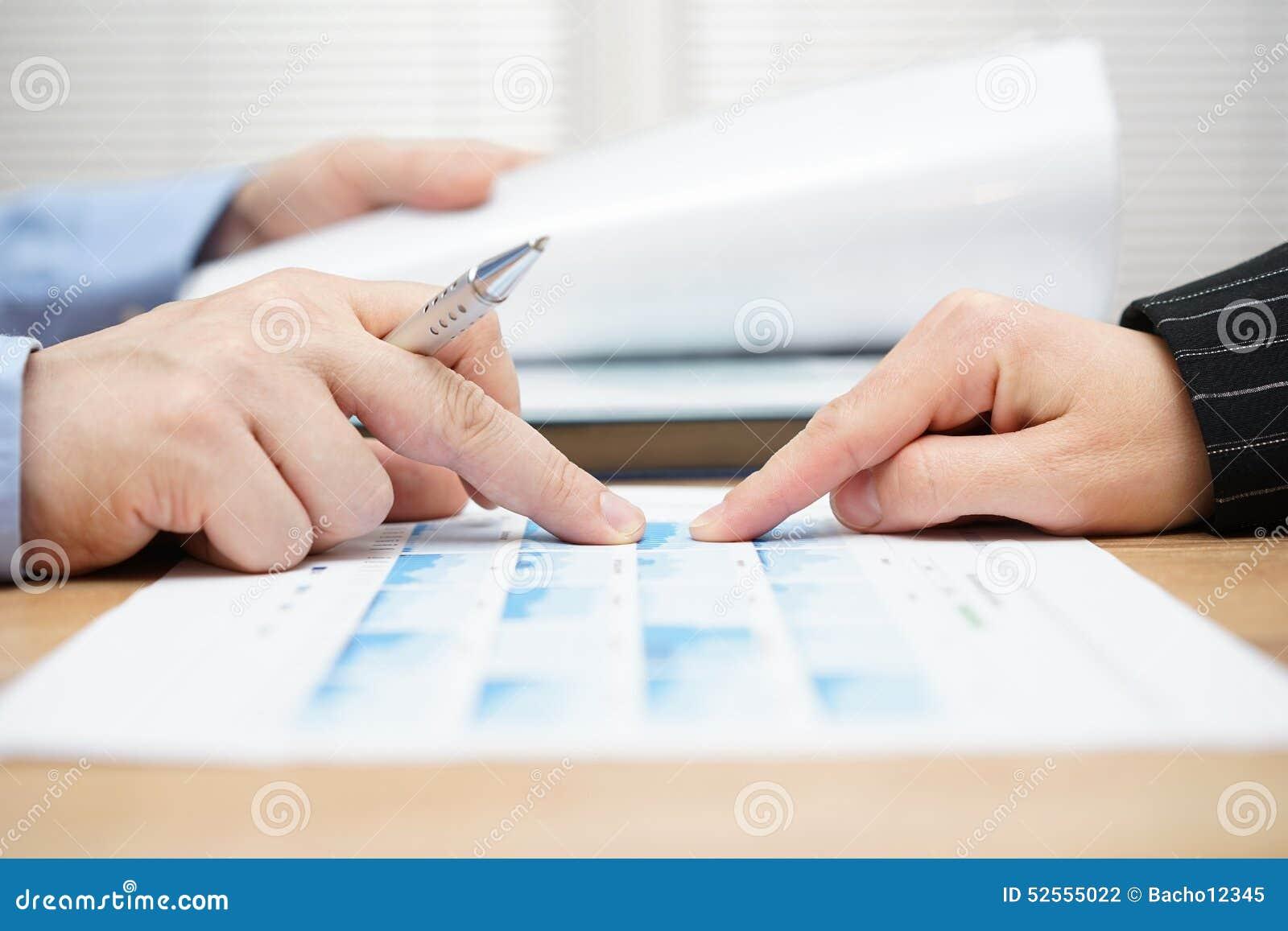 O homem de negócios está lendo o relatório e está discutindo dados comerciais com