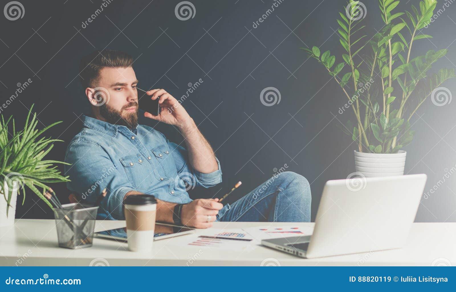 O homem de negócios farpado senta-se no escritório na tabela, inclinando-se para trás na cadeira e falando no telefone celular ao