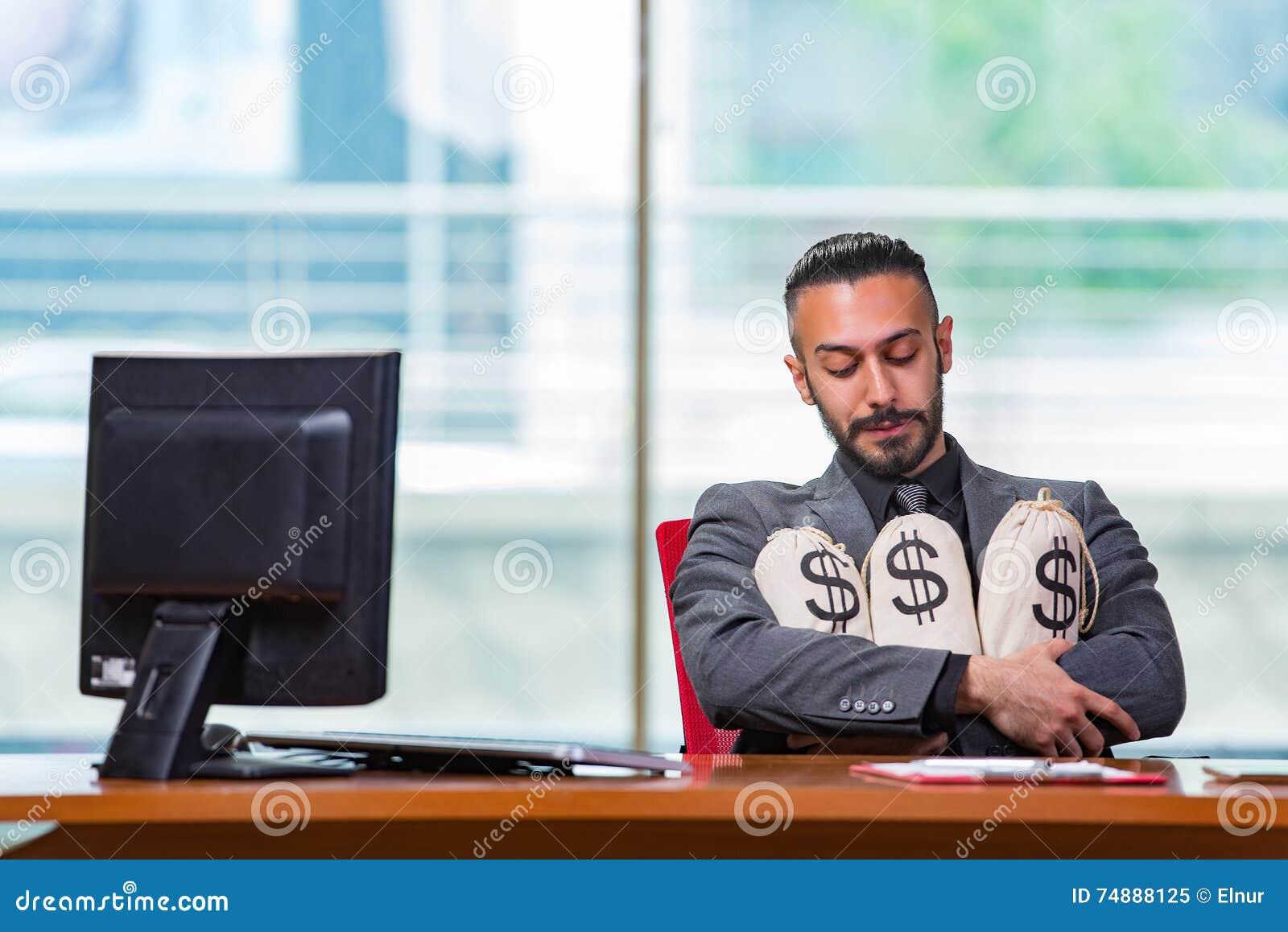 O homem de negócios feliz com os sacos do dinheiro no escritório