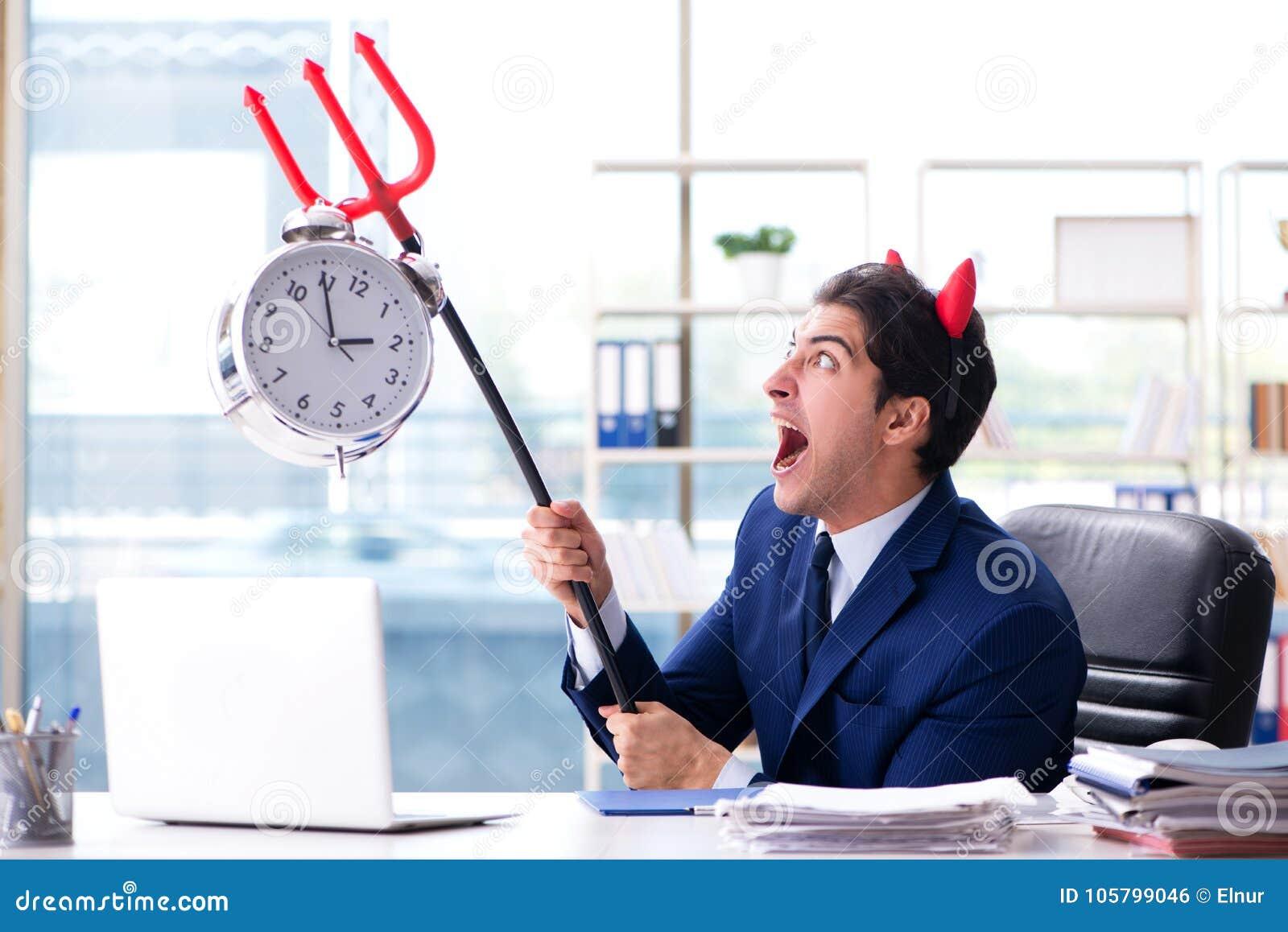 O homem de negócios irritado do diabo no escritório