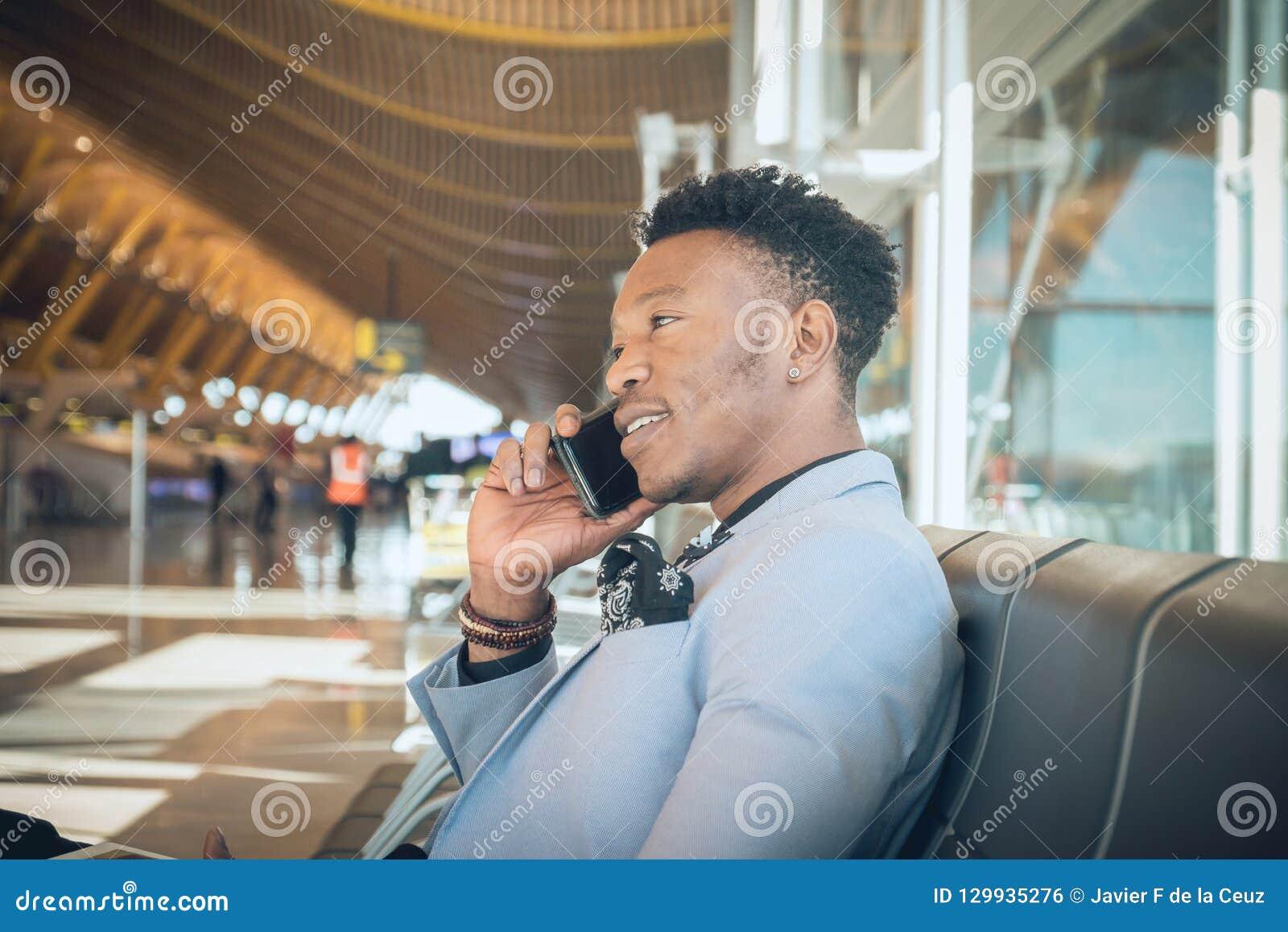 O homem de negócios novo é assentado no aeroporto que sorri e que fala b