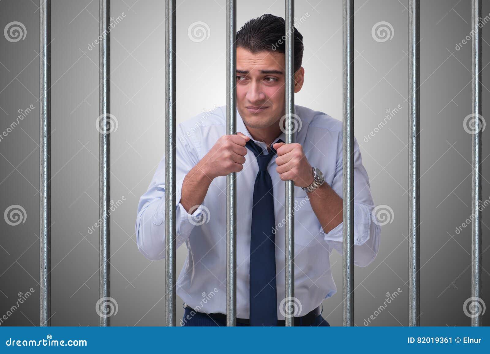 O homem de negócios novo atrás das barras na prisão
