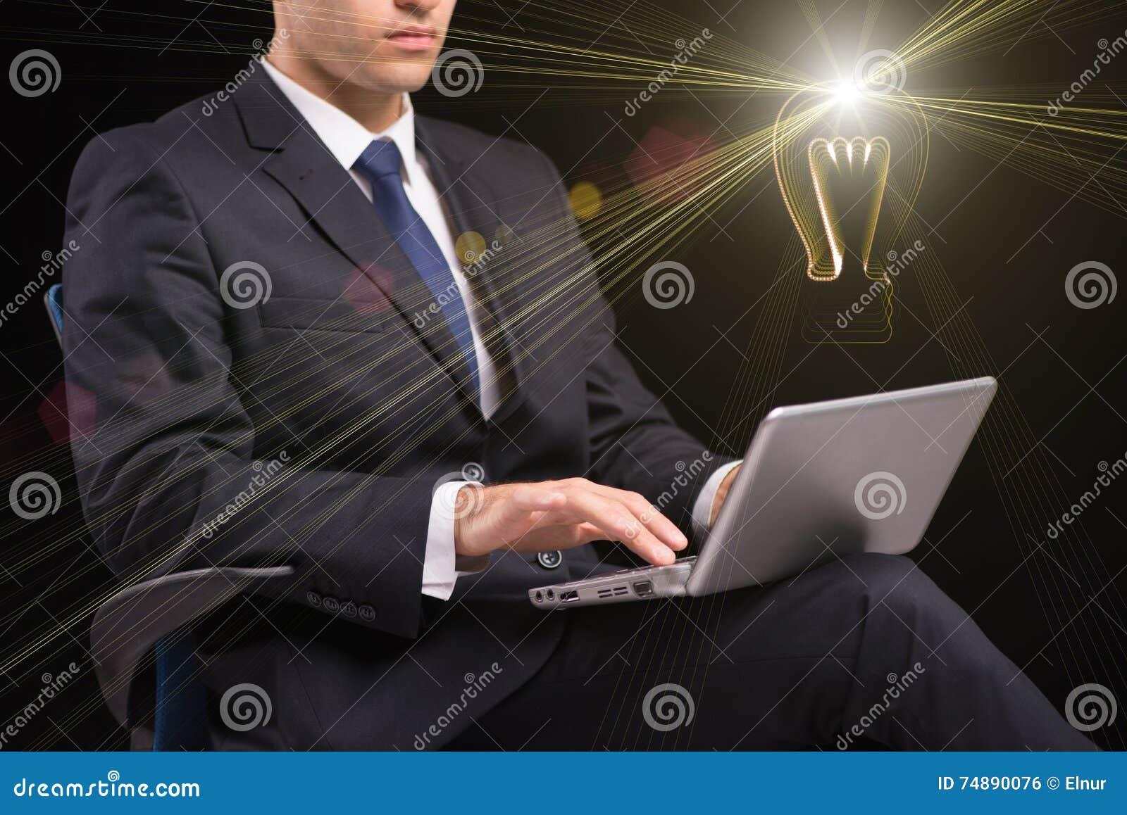 O homem de negócios novo com conceito da ideia do portátil e da lâmpada