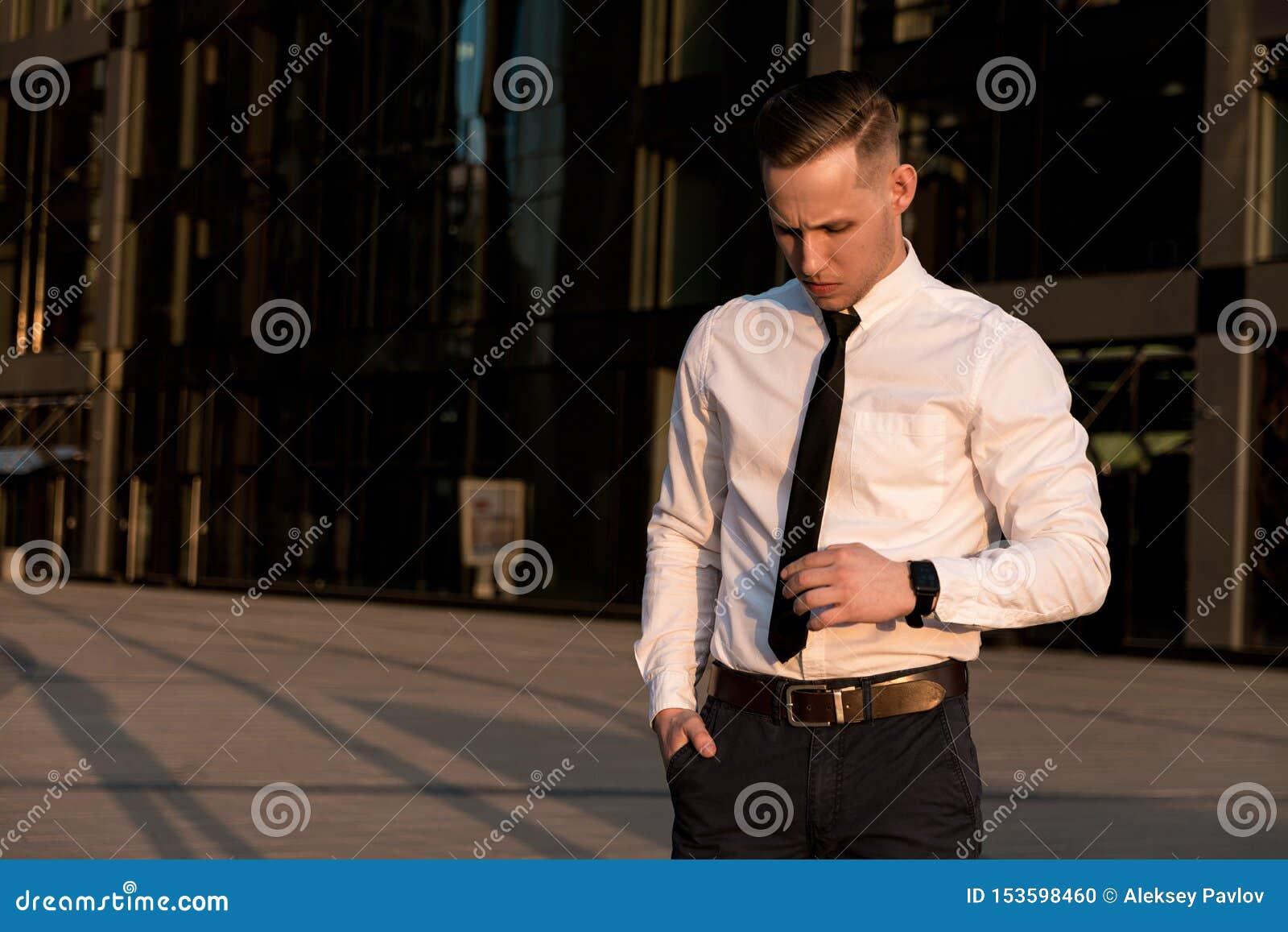 O homem de negócios novo corrige um laço