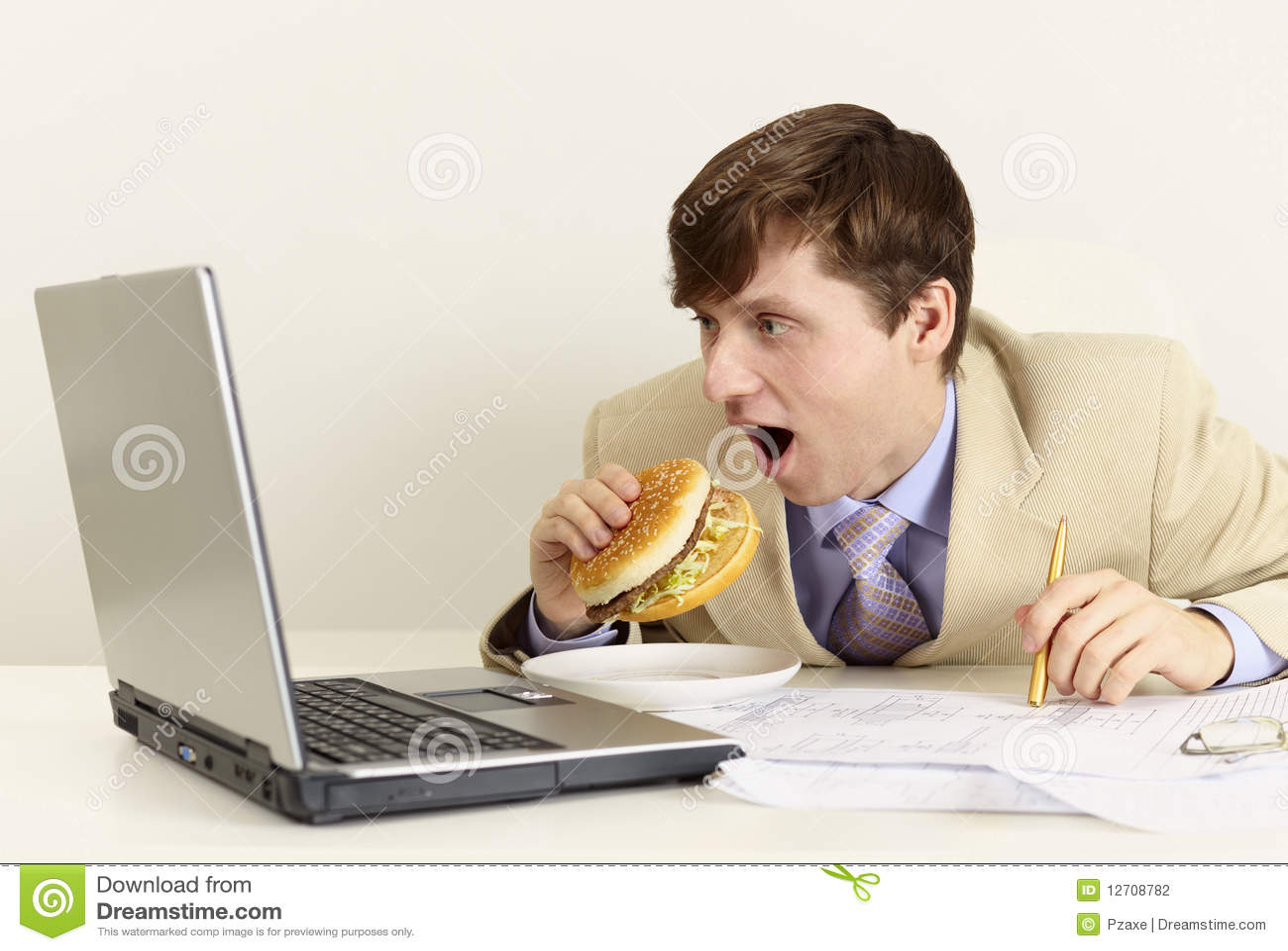 O homem de negócios novo está indo comer o sanduíche