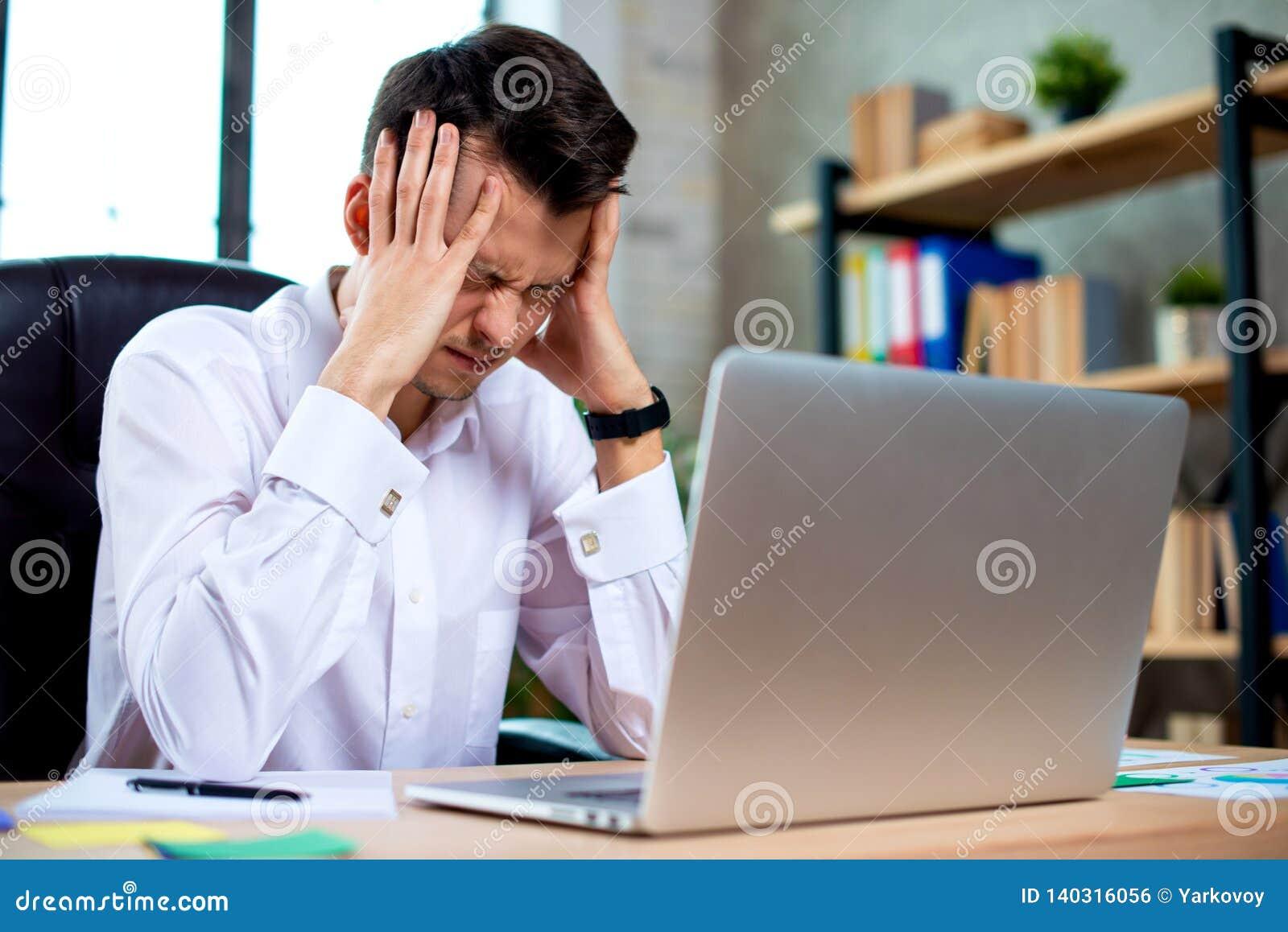 O homem de negócios novo forçado chocado por más notícias usando o portátil no trabalho, acionista falido desesperado perdeu o di