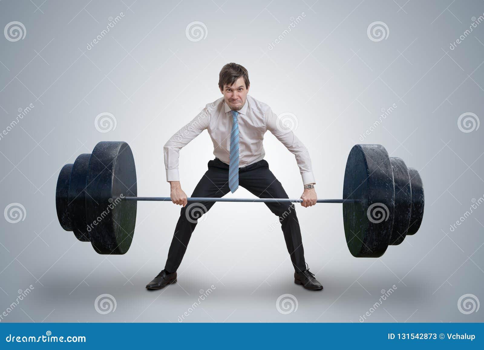 O homem de negócios novo na camisa está levantando pesos pesados