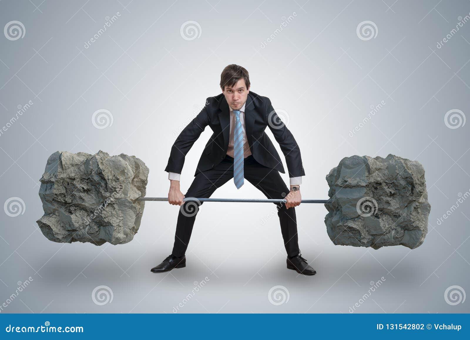 O homem de negócios novo no terno está levantando pesos pesados