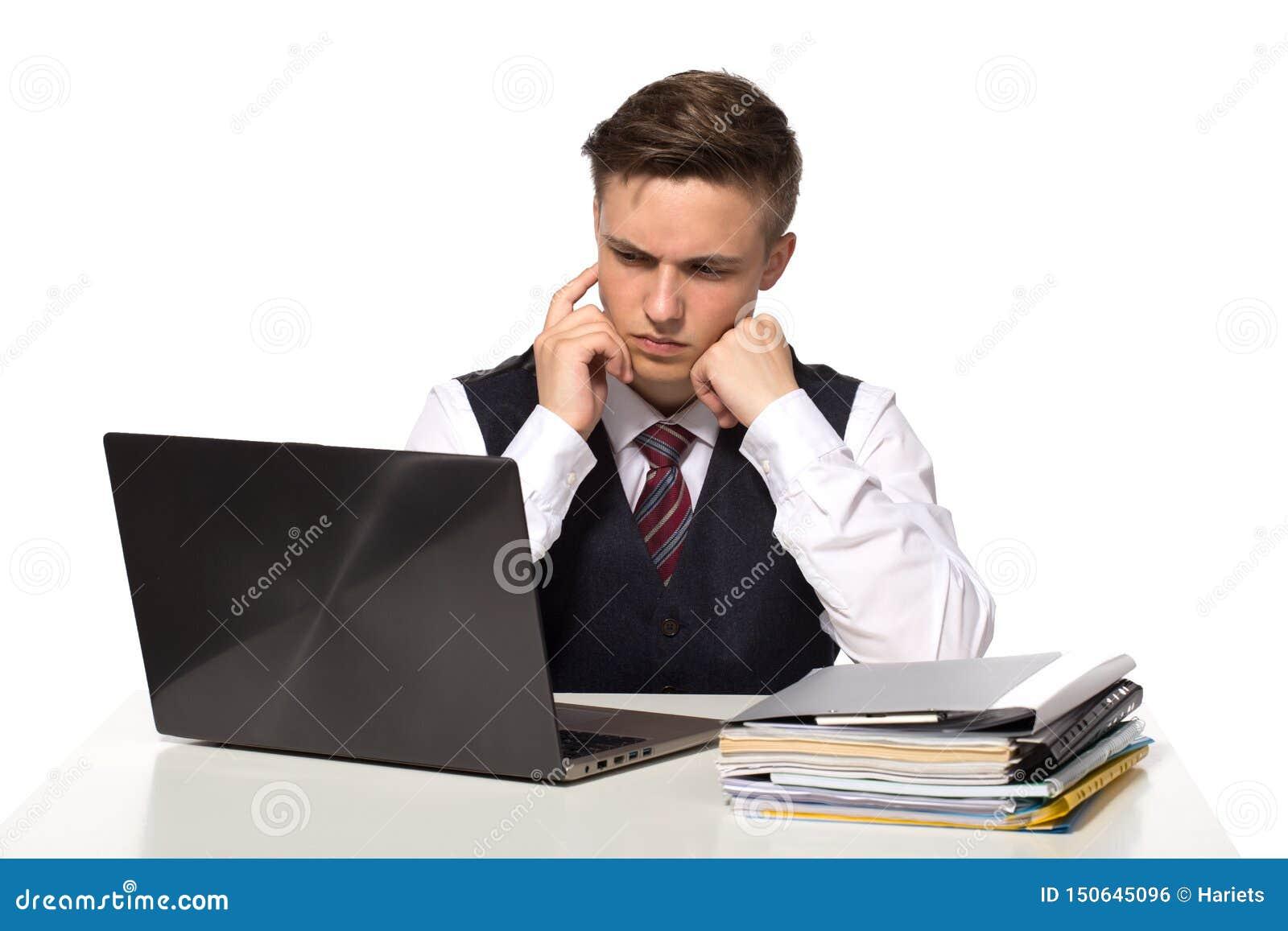 O homem de negócios pensativo novo calcula impostos na mesa no escritório Isolado no branco