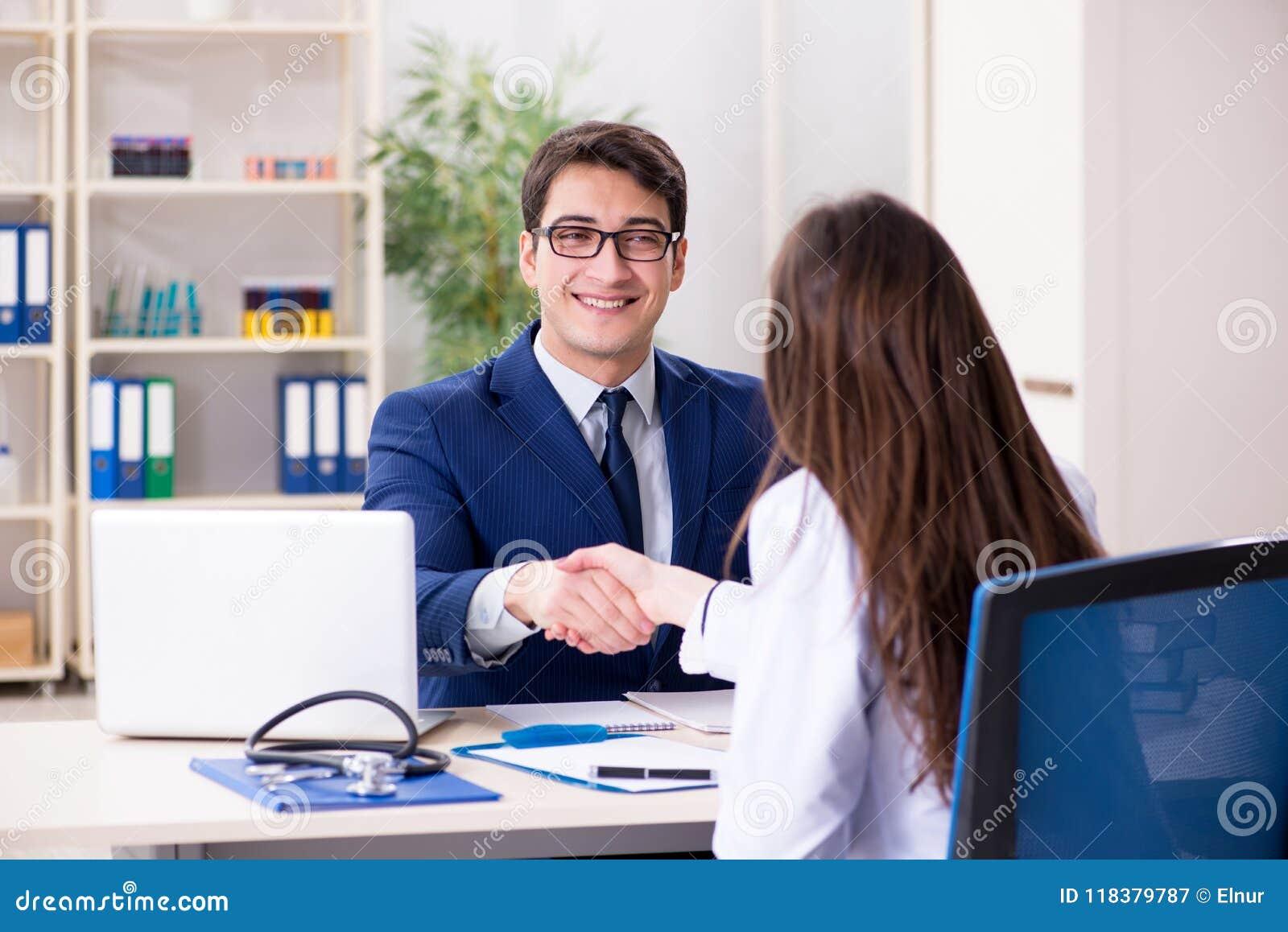 O homem de negócios que discute problemas de saúde com o doutor