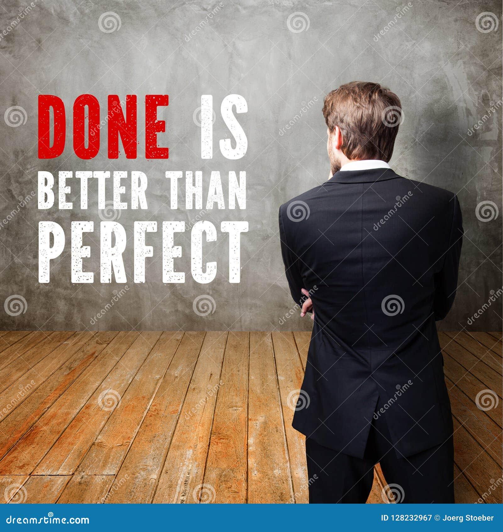O homem de negócios que está na frente de uma parede com o ` da mensagem feito é melhor do que perfeito o `