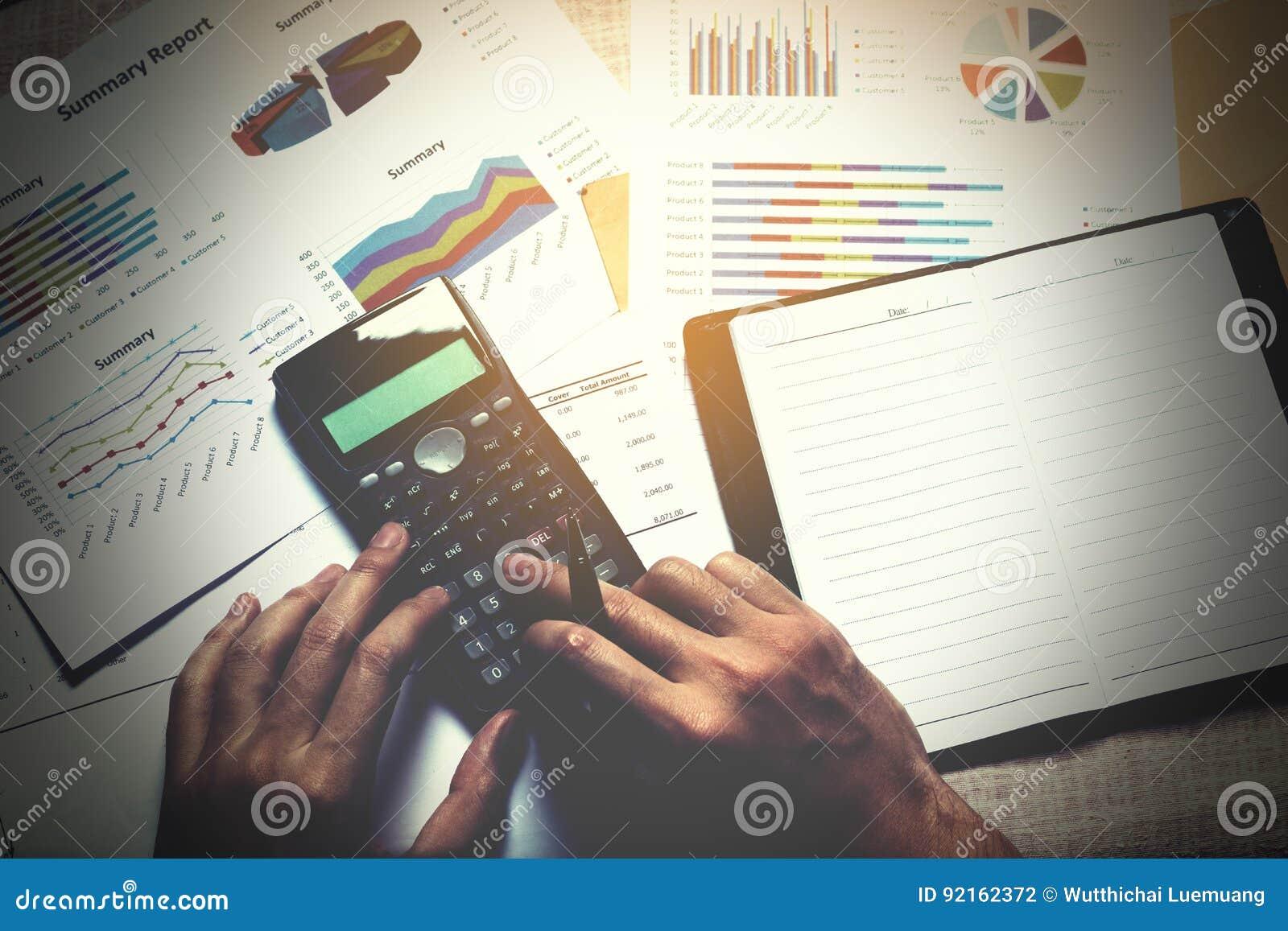 O homem de negócios que faz a finança e calcula na mesa com analyaing s