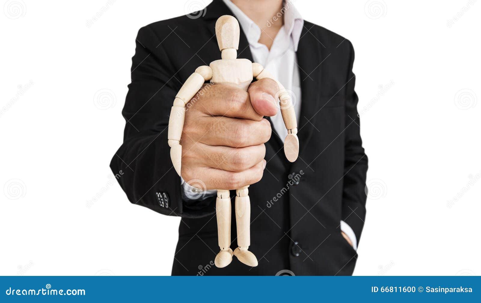 O homem de negócios que guarda a figura de madeira, conceito de toma o controle, oprimir-lo, e etc. , isolado sobre o fundo branc