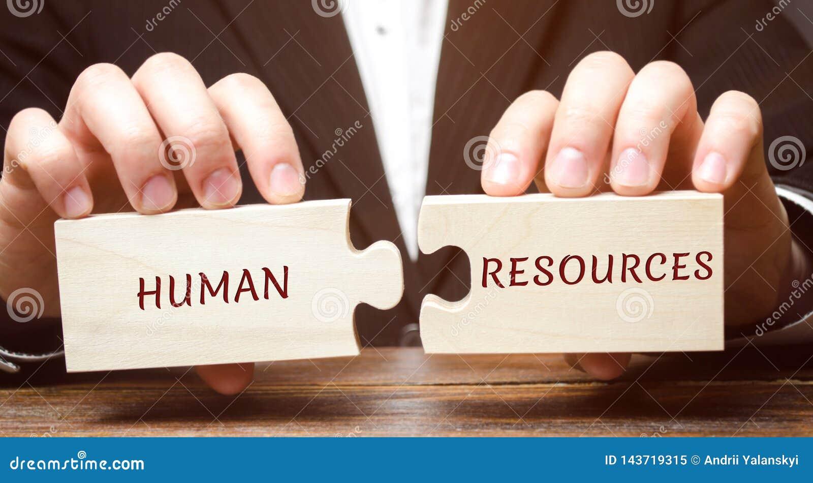 O homem de negócios recolhe enigmas de madeira com os recursos humanos da palavra Recrutamento, hora, liderança e teambuilding Ne