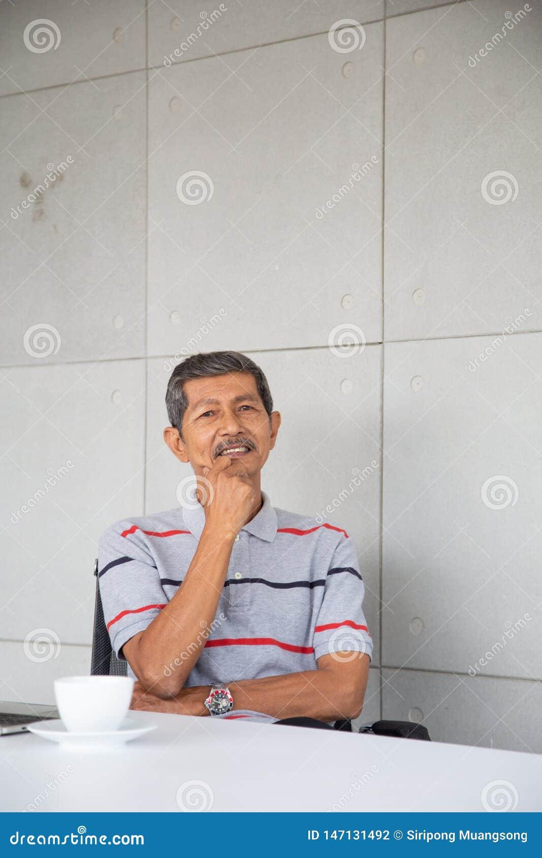 O homem de negócios superior de Ásia senta-se e sorri-se