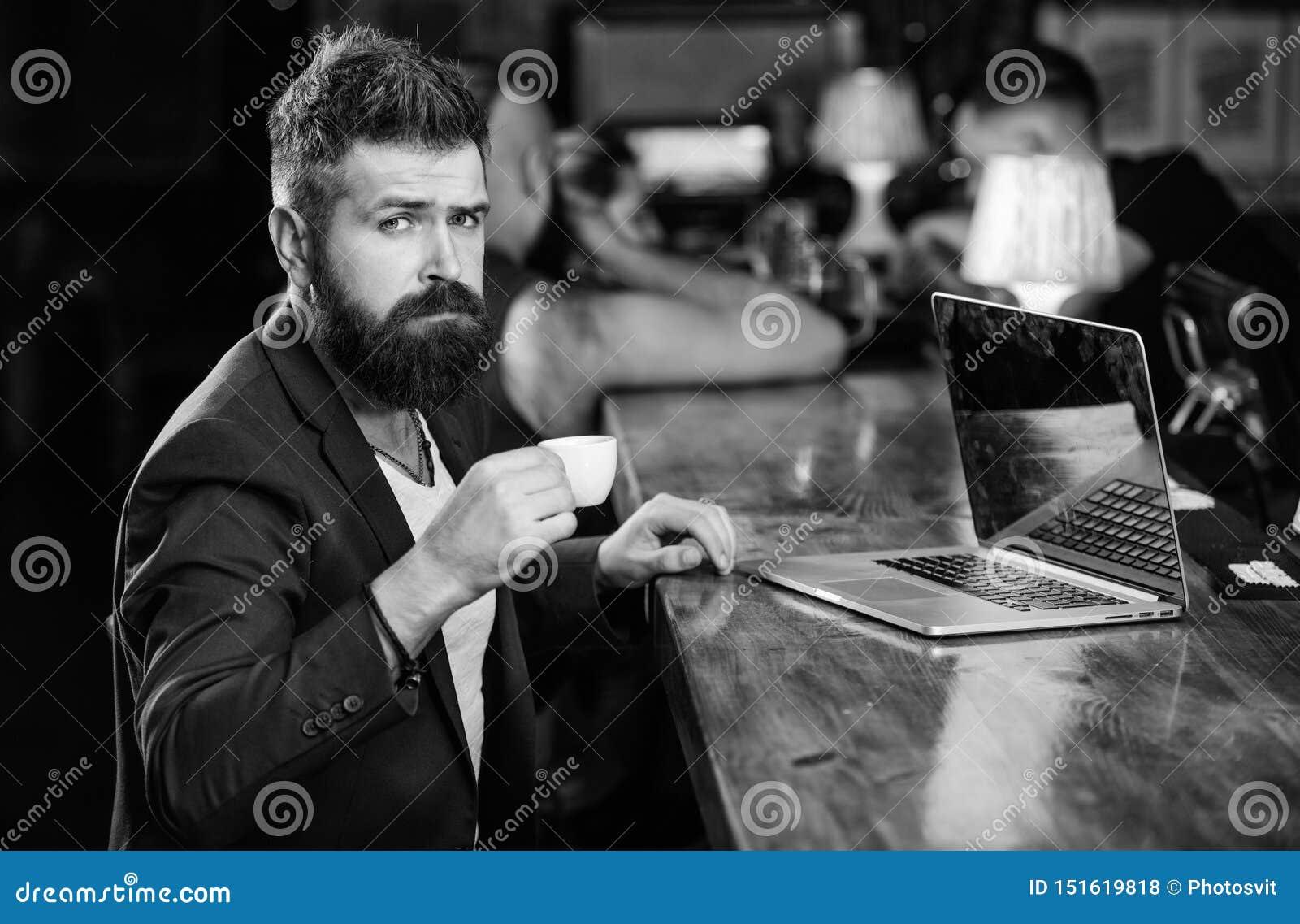 O homem de neg?cios farpado do homem senta o bar com port?til e x?cara de caf? Benef?cio aut?nomo Trabalho do gerente em linha qu