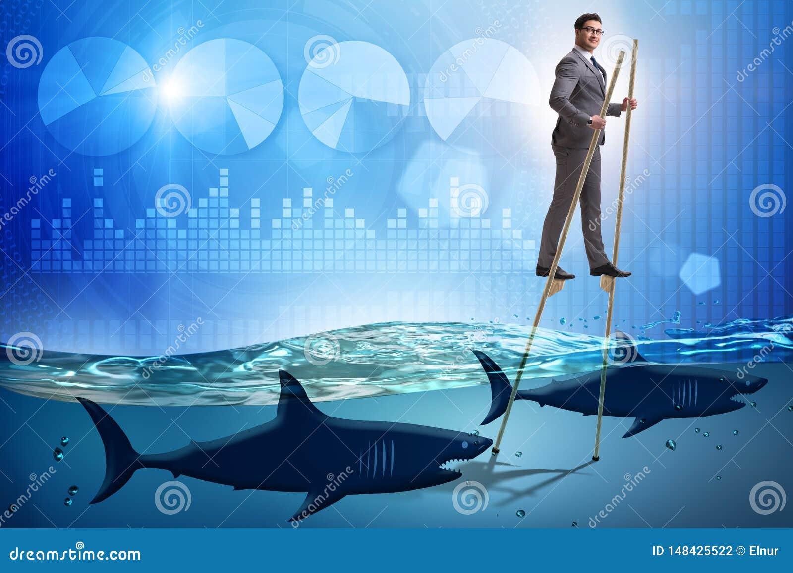 O homem de neg?cios que anda em pernas de pau entre tubar?es