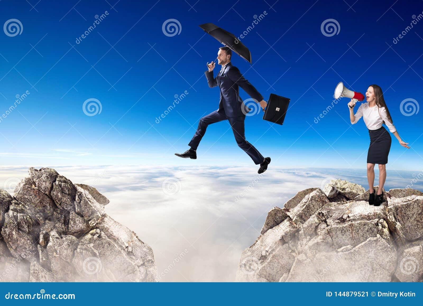 O homem de neg?cios que salta sobre um penhasco e um colega cheering com megafone