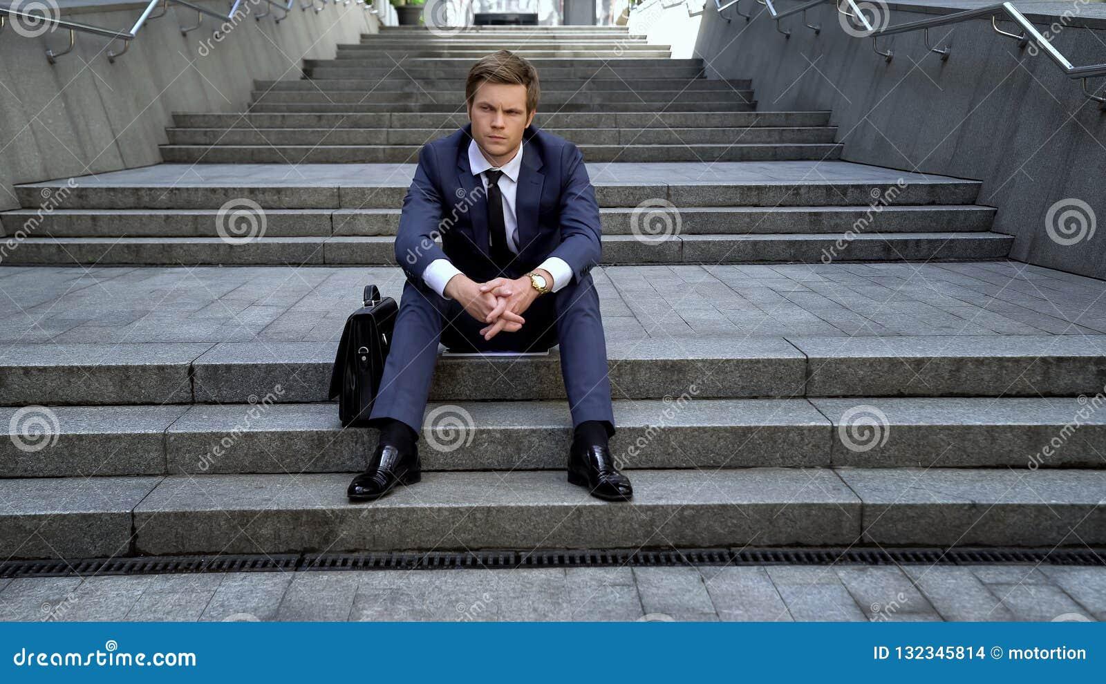 O homem decepcionado no terno que senta-se nas escadas, más entrelaça, oportunidades perdidas