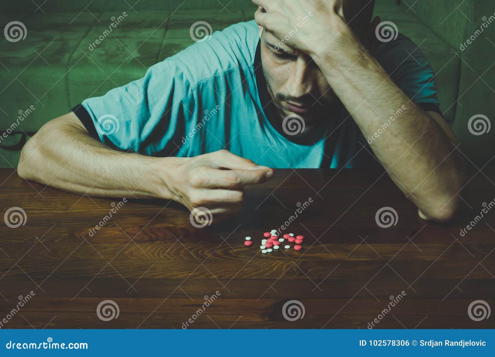 O homem deprimido que sofre da depressão suicida quer cometer o suicídio tomando drogas fortes do medicamento e os comprimidos e