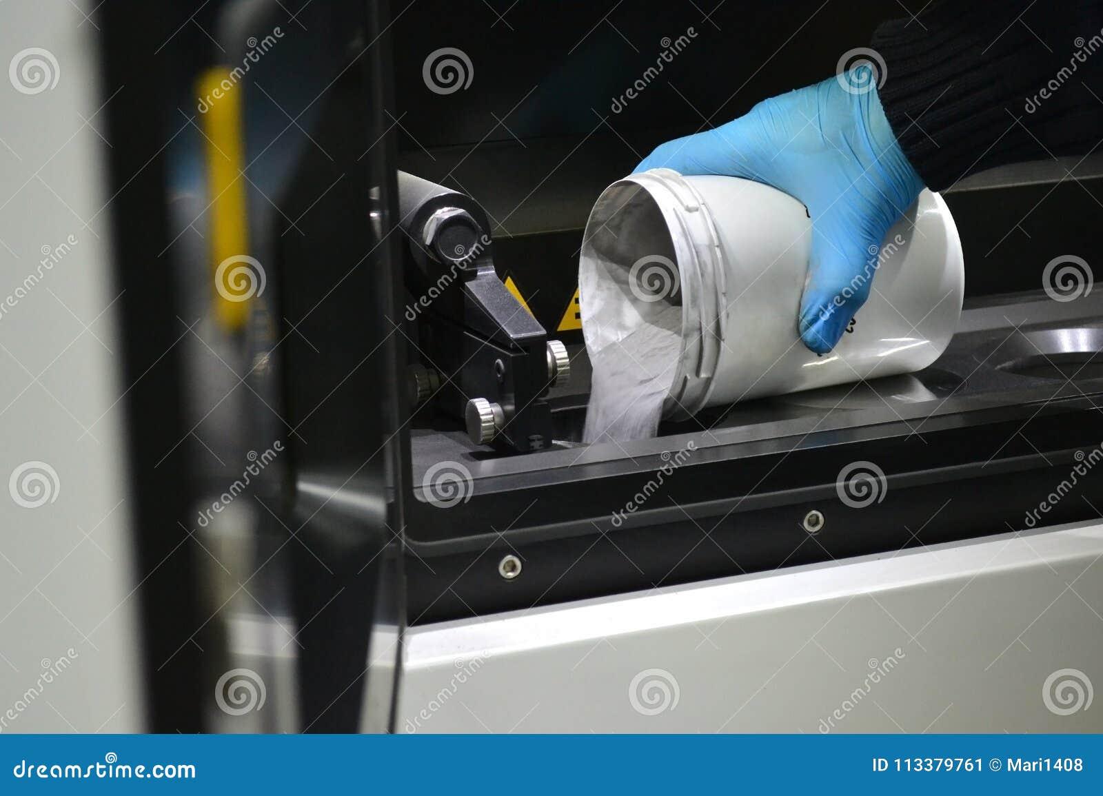 O homem derrama o pó de metal na câmara de uma máquina da aglomeração do laser