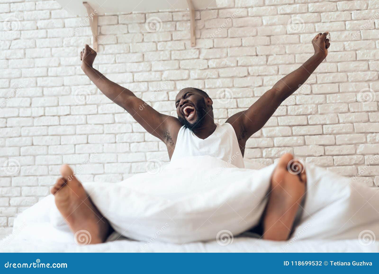 O homem despertado feliz é esticado para fora na cama