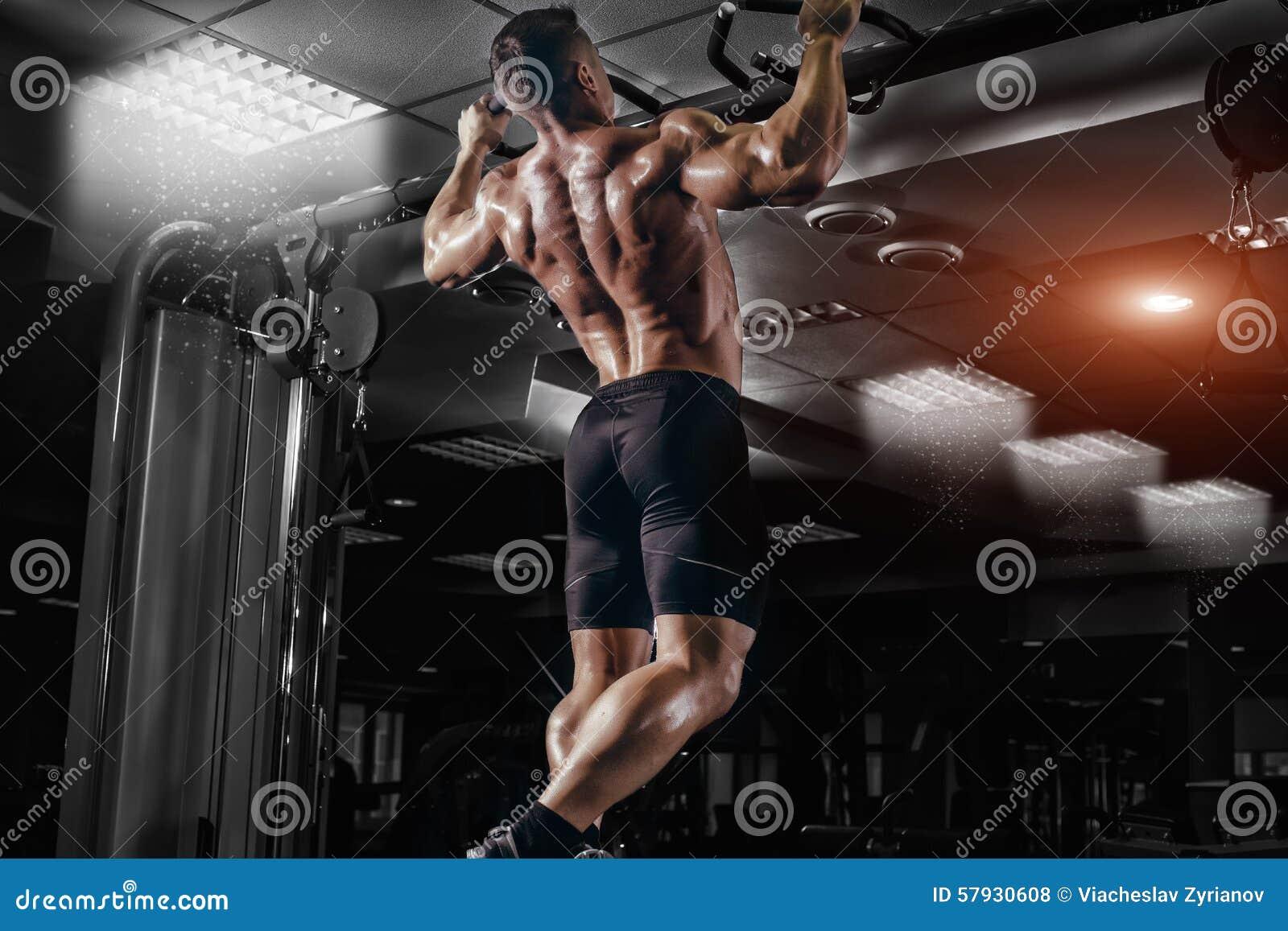 O homem do atleta do músculo na fatura do gym levanta