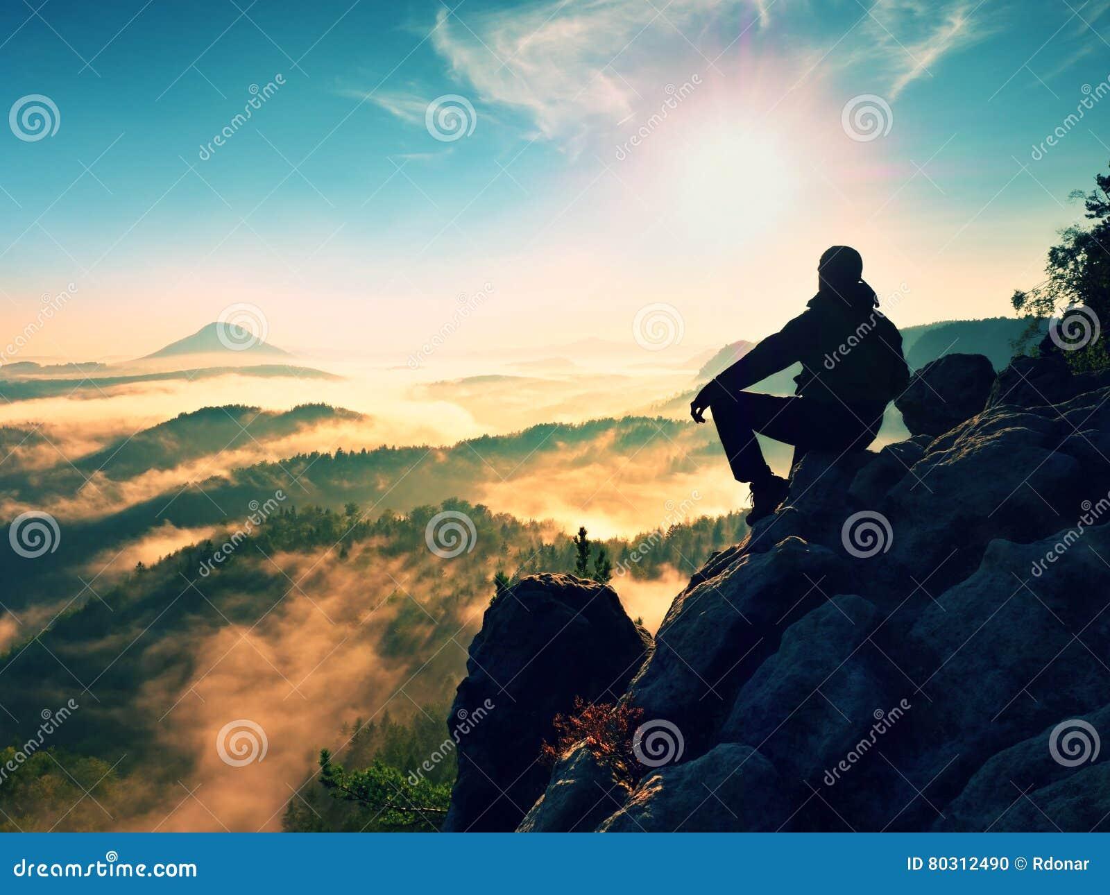 O homem do caminhante toma um resto no pico de montanha O homem coloca na cimeira, vale do outono do fole