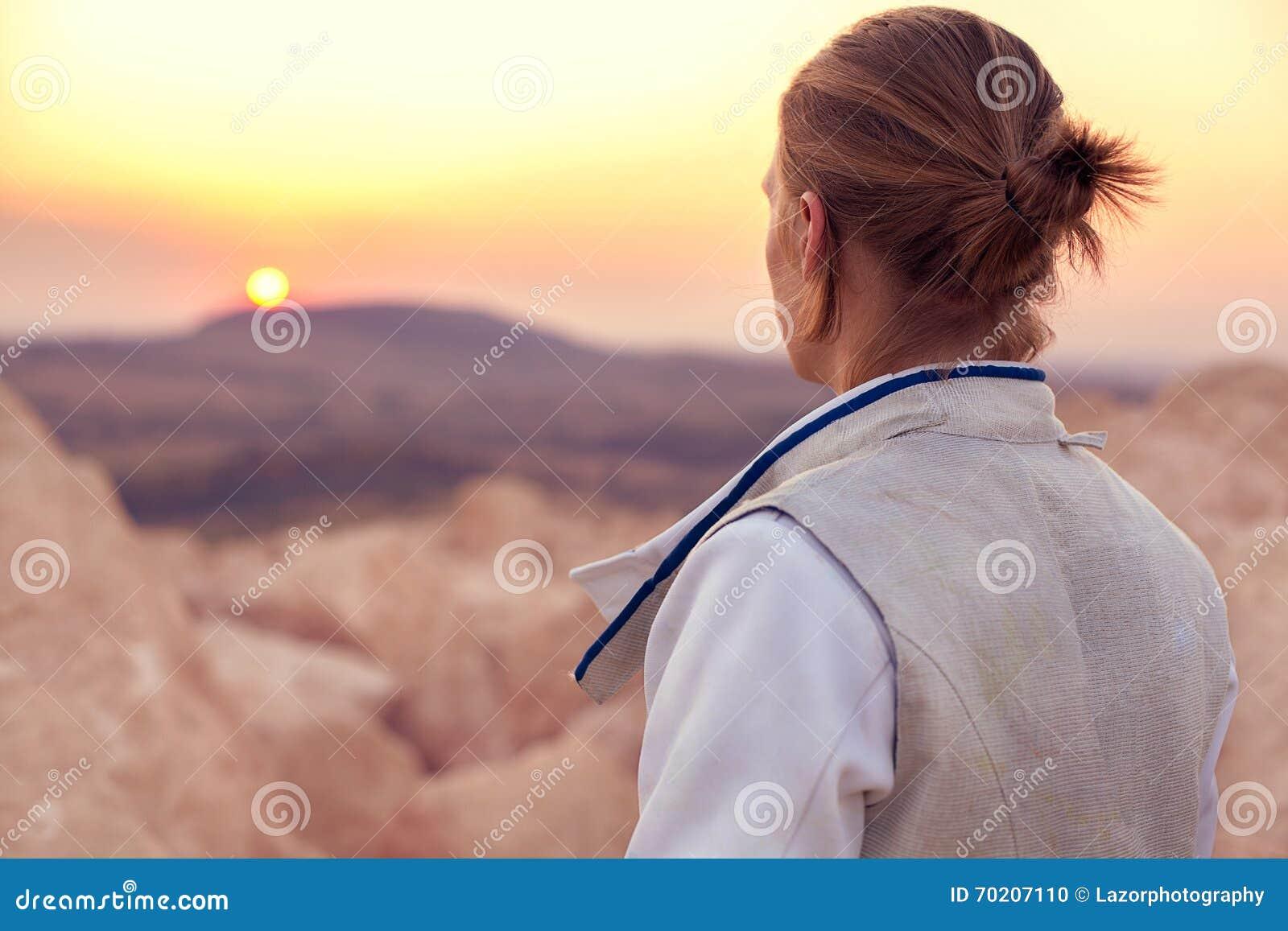 O homem do esgrimista no fundo rochoso e na vista para a frente ao sol vai para baixo