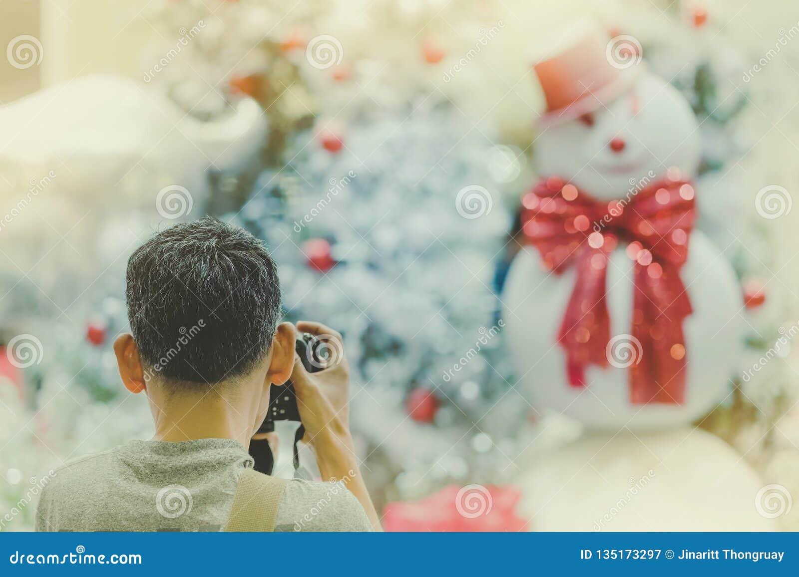 O homem do fotógrafo toma a foto da árvore de Natal decorada e de um sn