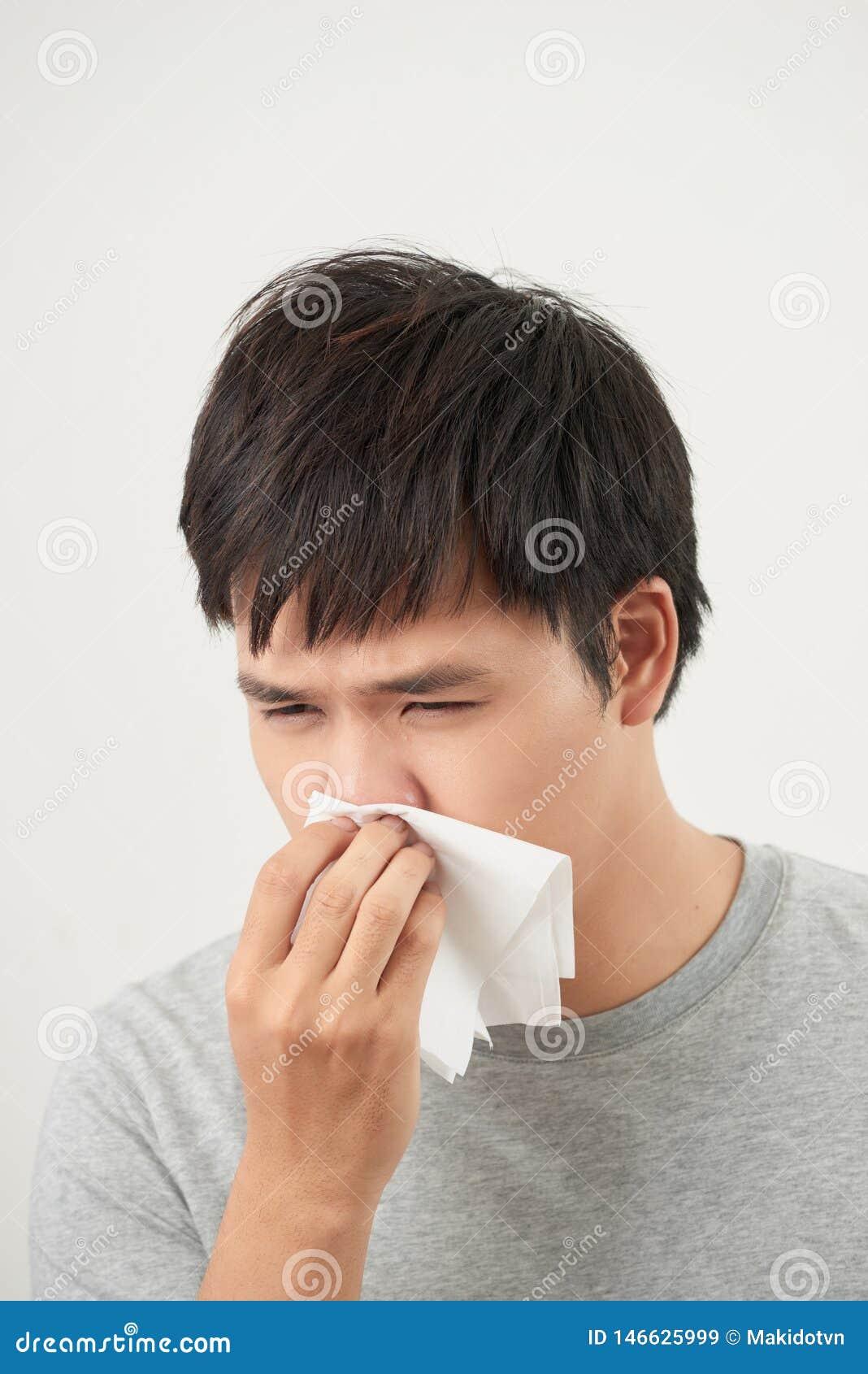 O homem ? doente e espirrando com fundo branco, asi?tico