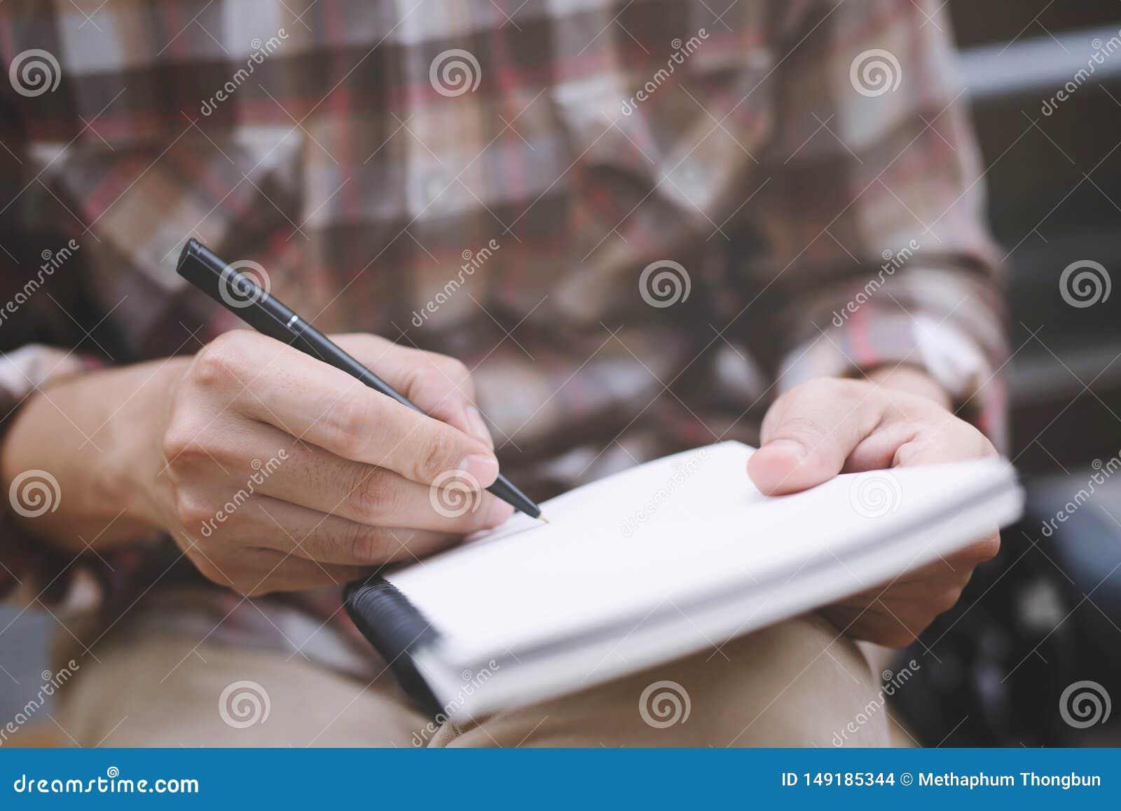 O homem dos povos da m?o est? sentando-se em uma cadeira de madeira usando a pena que escreve a almofada de nota da leitura do re