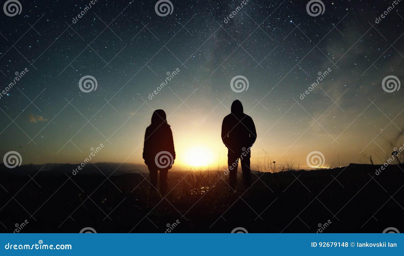 O homem e a mulher de um par povos estão no por do sol da lua sob o céu estrelado com estrelas brilhantes e uma Via Látea