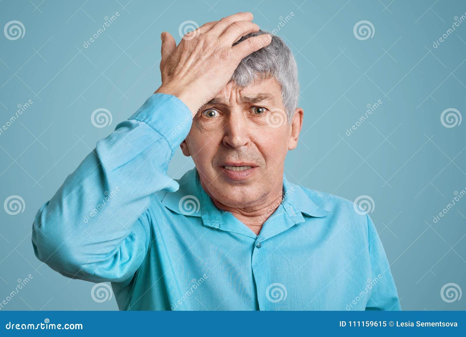 O homem elederly enrugado considerável esquecido na camisa azul, mantém a mão na cabeça, sente desesperadamente como esquece sobr