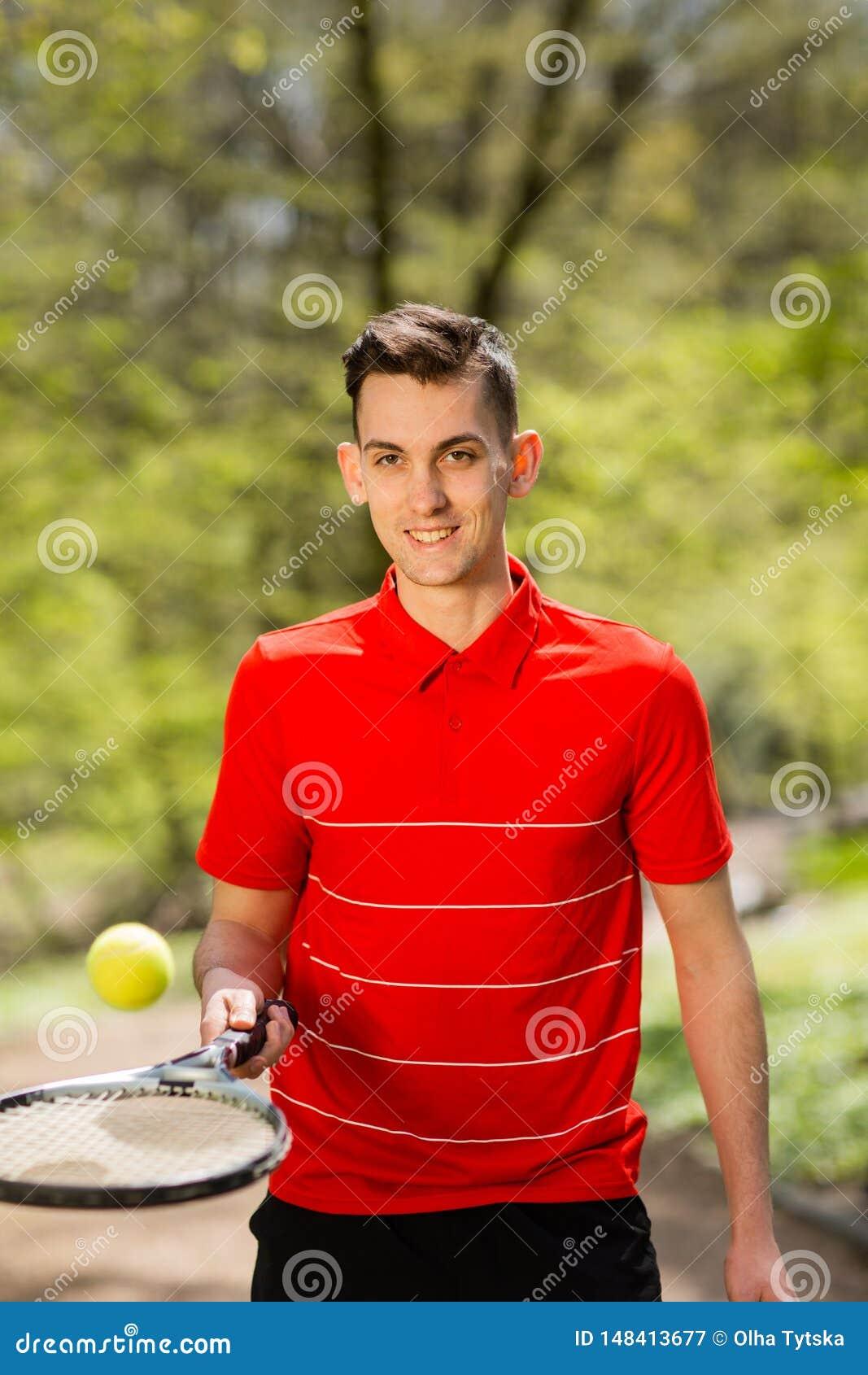 O homem em uma pose vermelha do t-shirt com uma raquete de t?nis e uma bola no fundo do parque verde Conceito do esporte