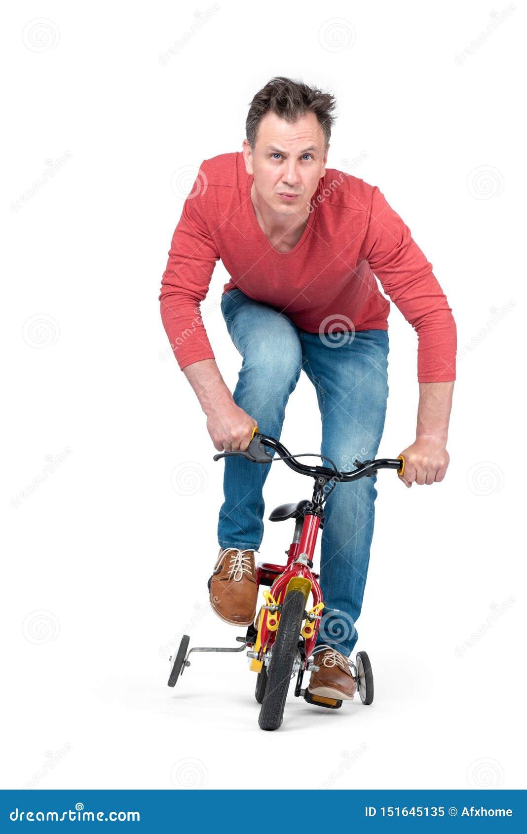 O homem engraçado nas calças de brim e em um t-shirt vermelho está rolando em uma bicicleta das crianças Front View Isolado no fu