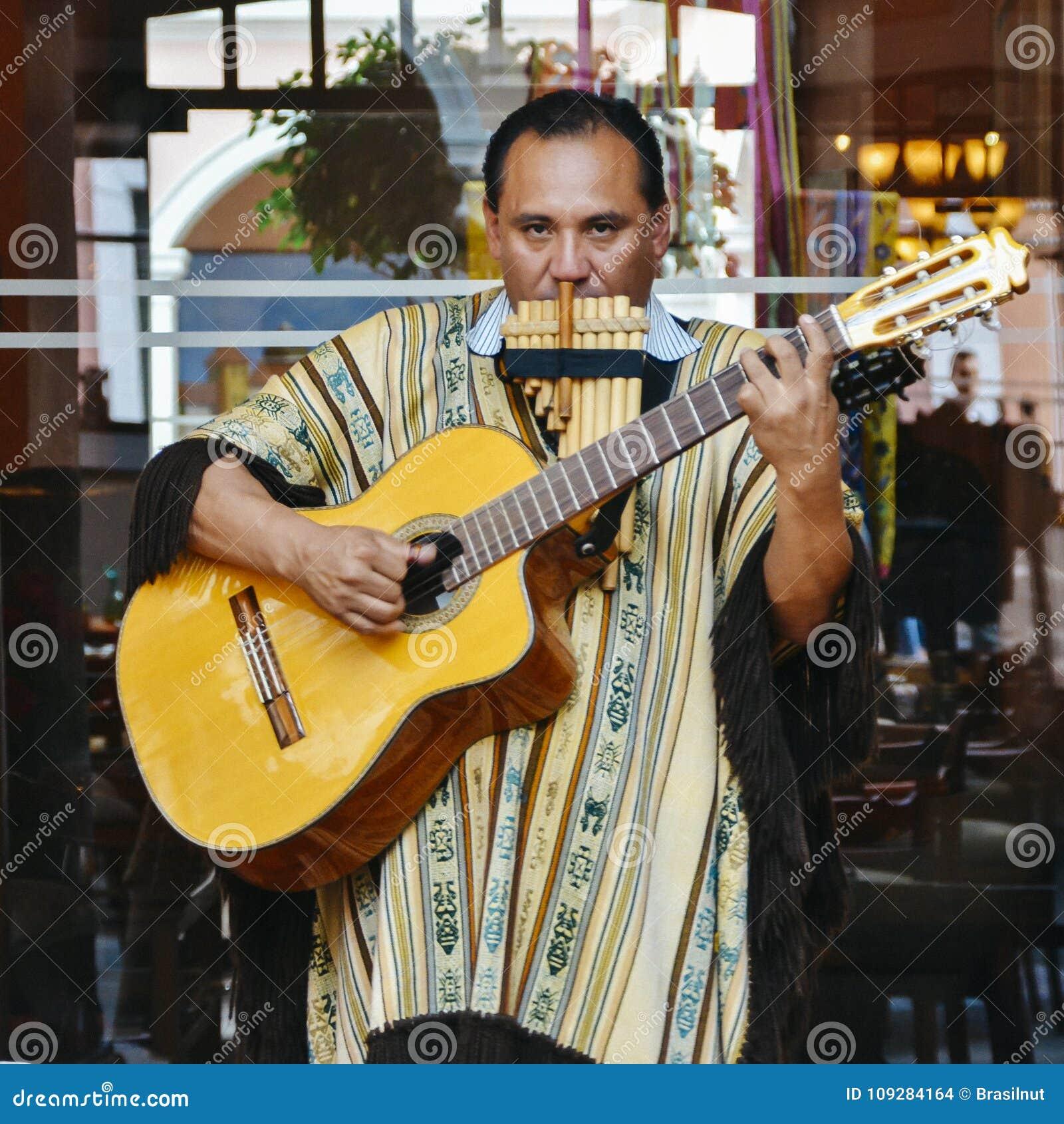 O homem equatoriano local joga a guitarra e a flauta na rua