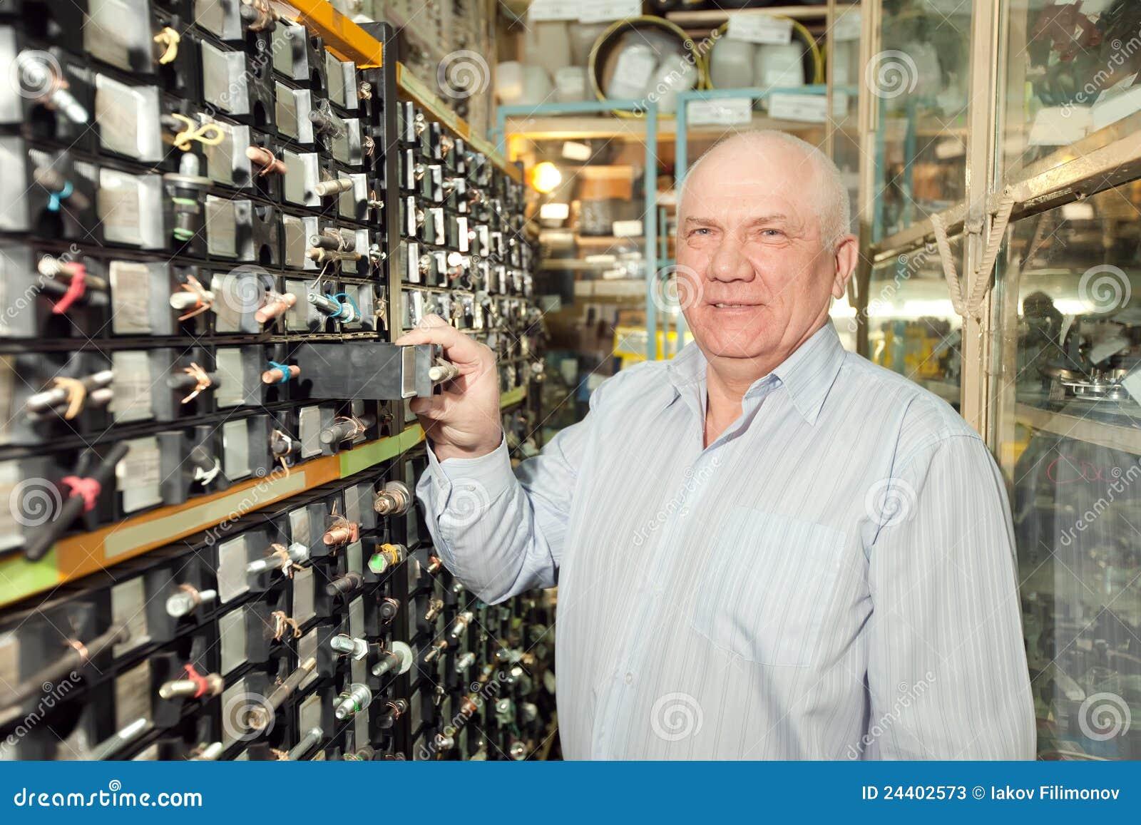 O homem escolhe prendedores na loja das peças de automóvel