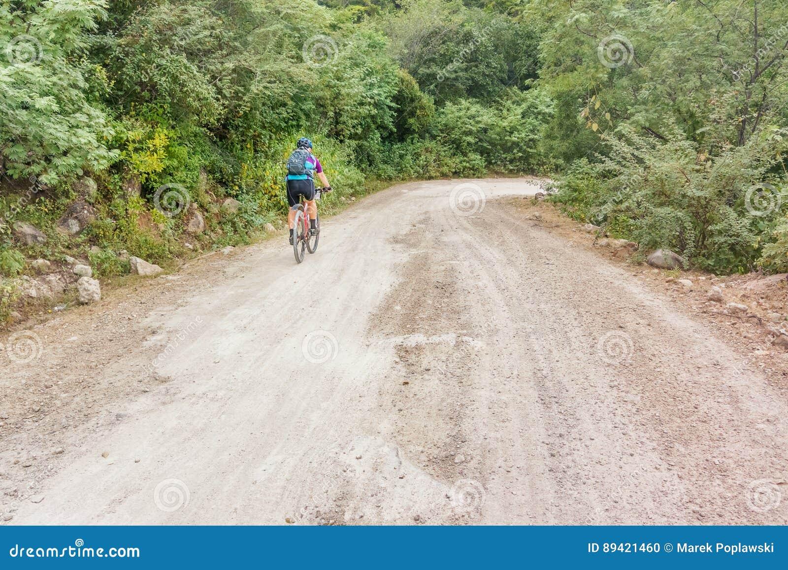 O homem está dando um ciclo na estrada de terra nas Honduras