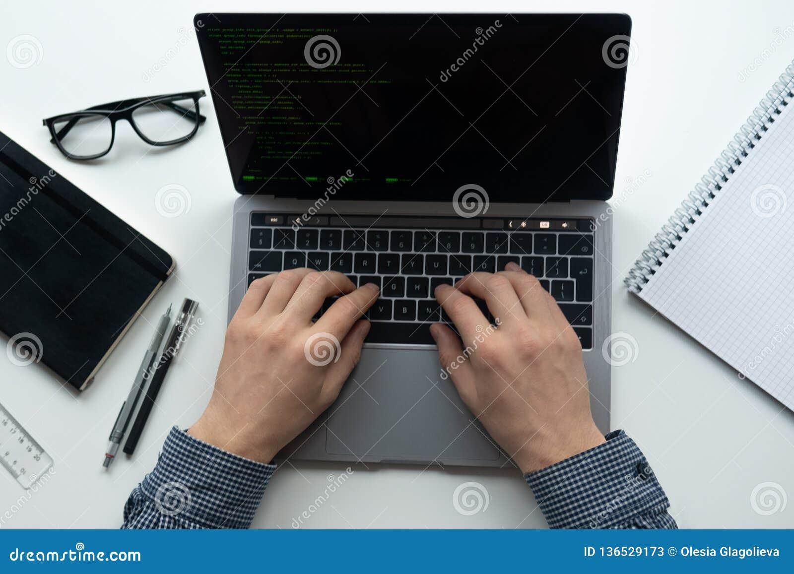 O homem está datilografando em seu portátil na tabela branca Vista superior, configuração lisa