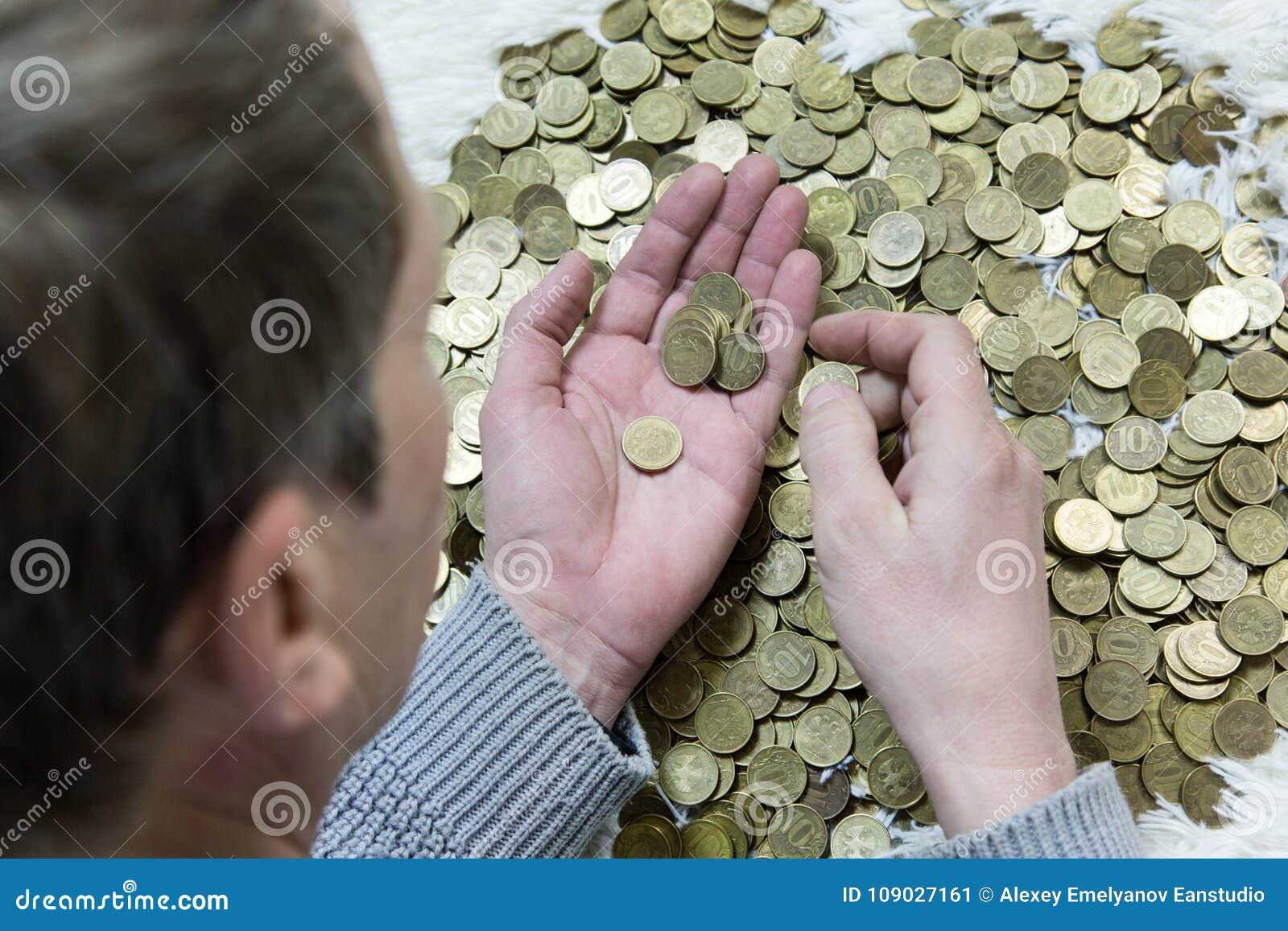 O homem está guardando moedas